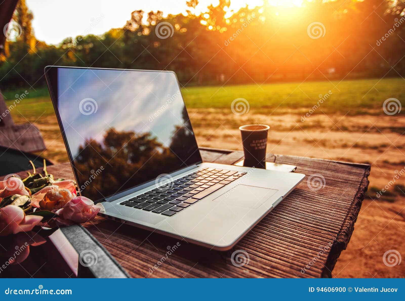 Laptop na szorstkim drewnianym stole z filiżanką i bukiecie peonie kwitnie w plenerowym parku