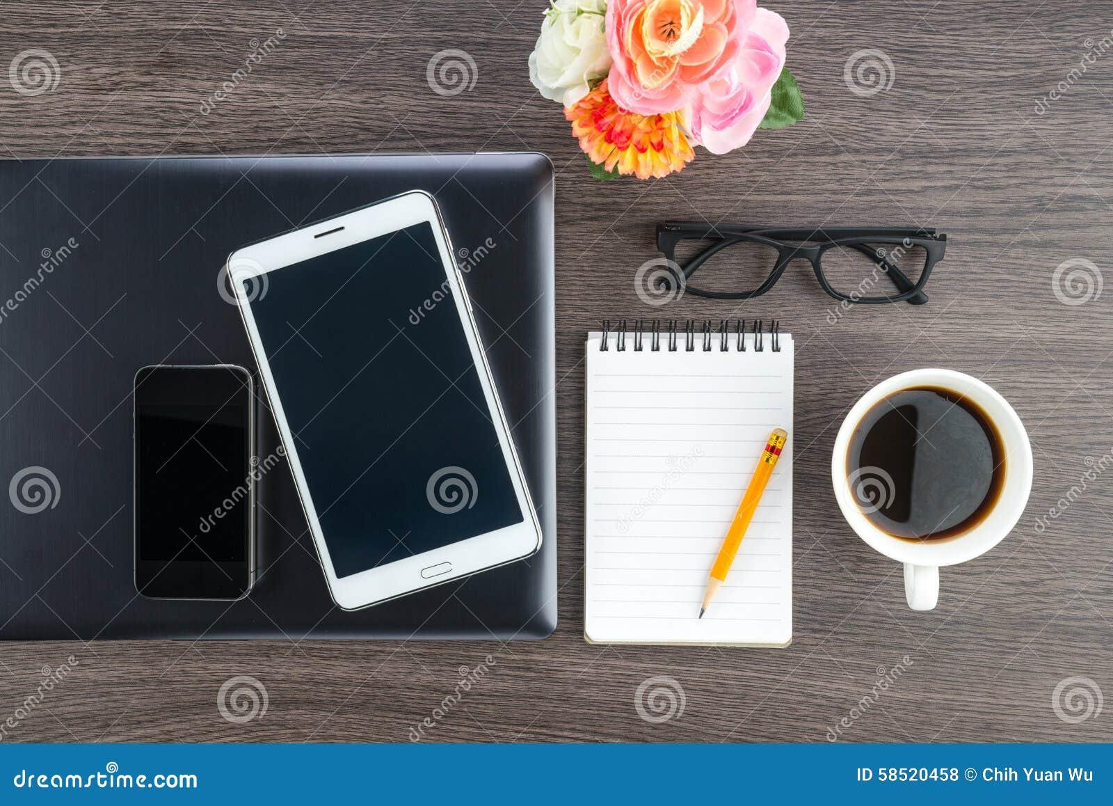 Laptop pastylka z notatnikiem na biurku i telefon komórkowy
