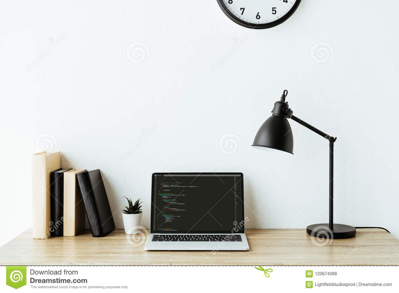 laptop with program code and books on work desk