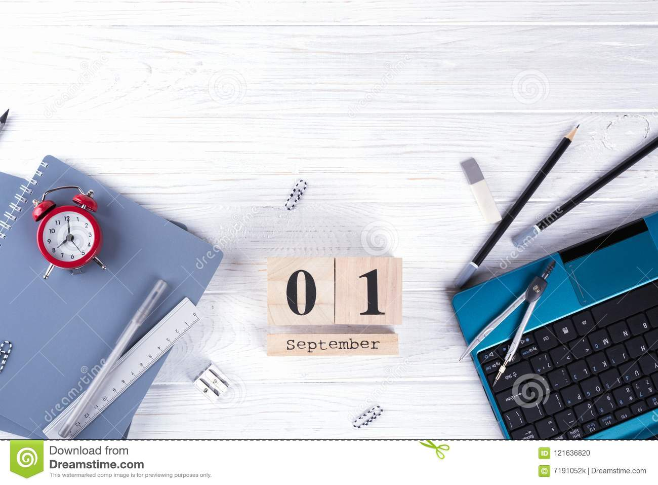 Laptop, red alarm clock and supplies, wooden calendar with date 1st September. on white desk. Back to school concept.