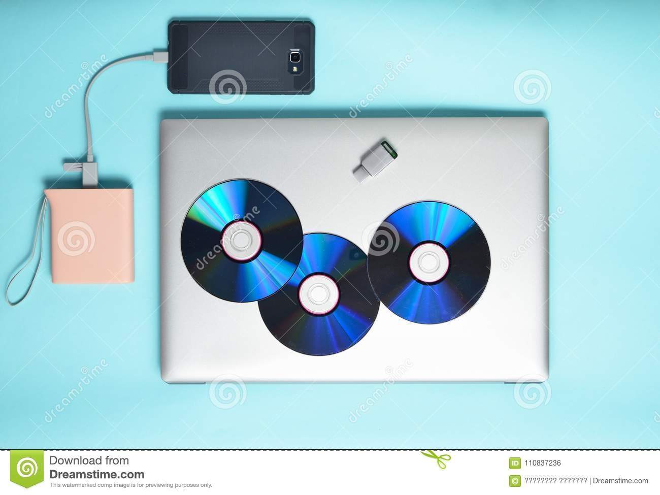 Laptop, smartphone, power bank, CD drives, USB flash drive on a blue background. Modern and outdated digital media and gadgets