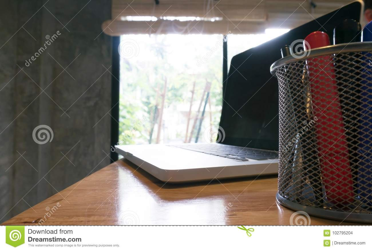 Laptop stands on a wooden table.