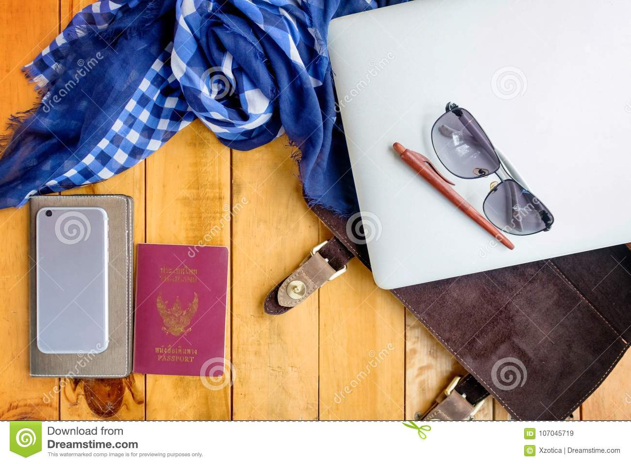 Leather bag notebook and blue check scarf on wood table