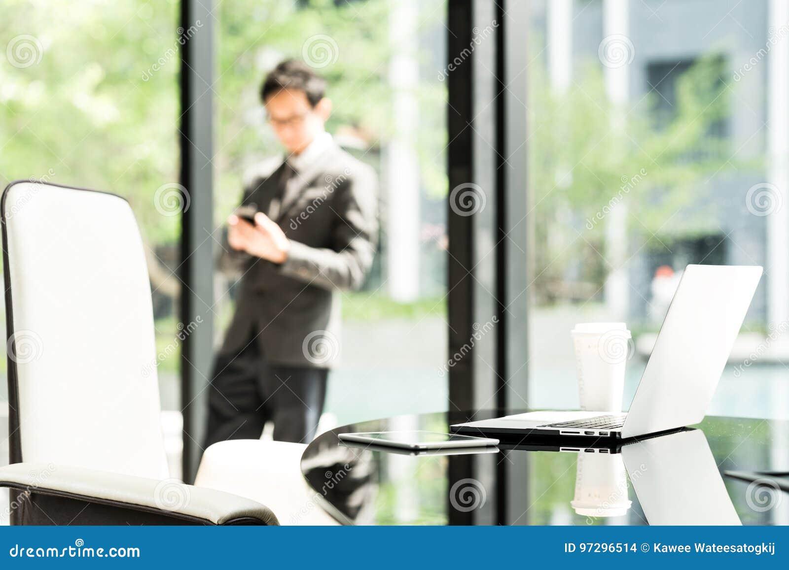 Laptop, tabuleta digital, e café na tabela do executivo ou do gerente no escritório moderno do homem de negócios ou do empresário