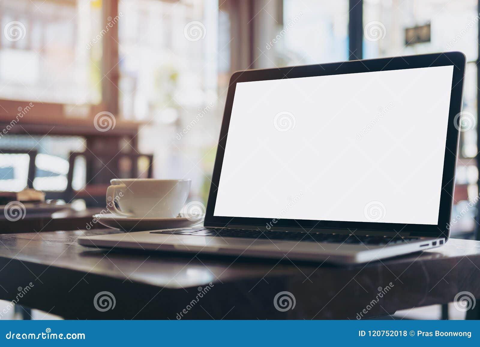Laptop z pustym bielu ekranem na drewnianym stole w nowożytnej loft kawiarni