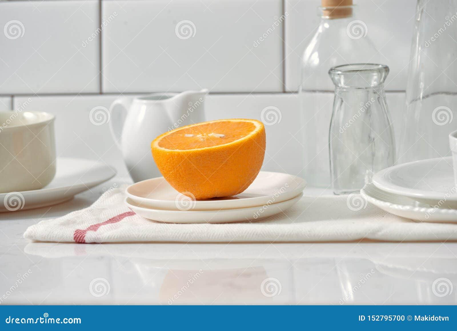 Laranja em um prato na tabela na cozinha