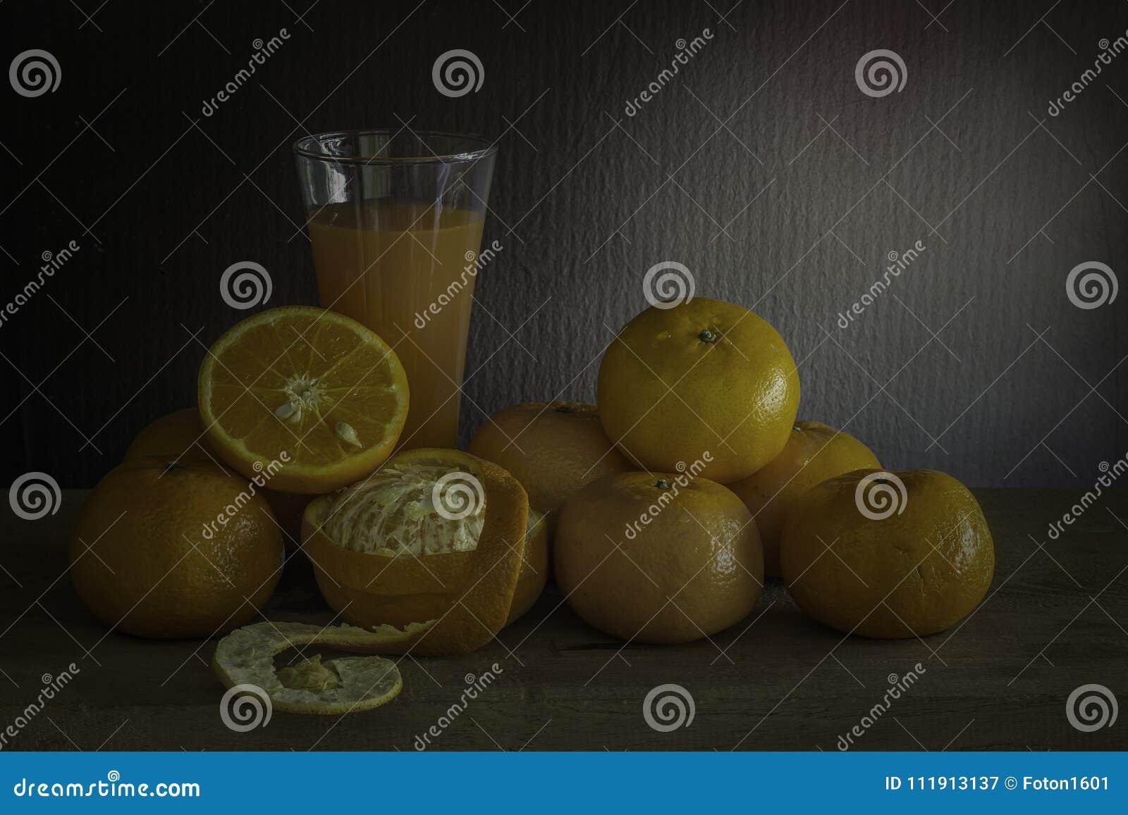 Laranjas e vidro do suco em uma tabela de madeira / Ainda fruto da vida