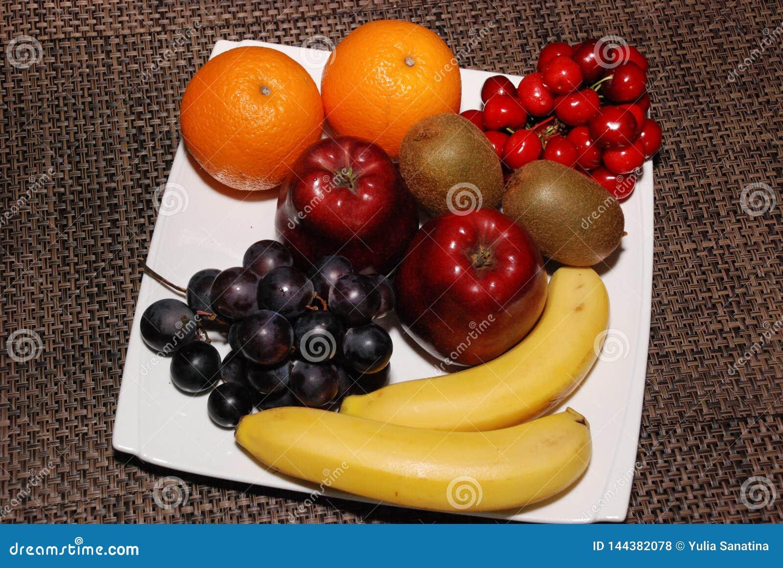 Laranjas, maçãs, uvas, quivis, cerejas, bananas na placa branca na tabela marrom
