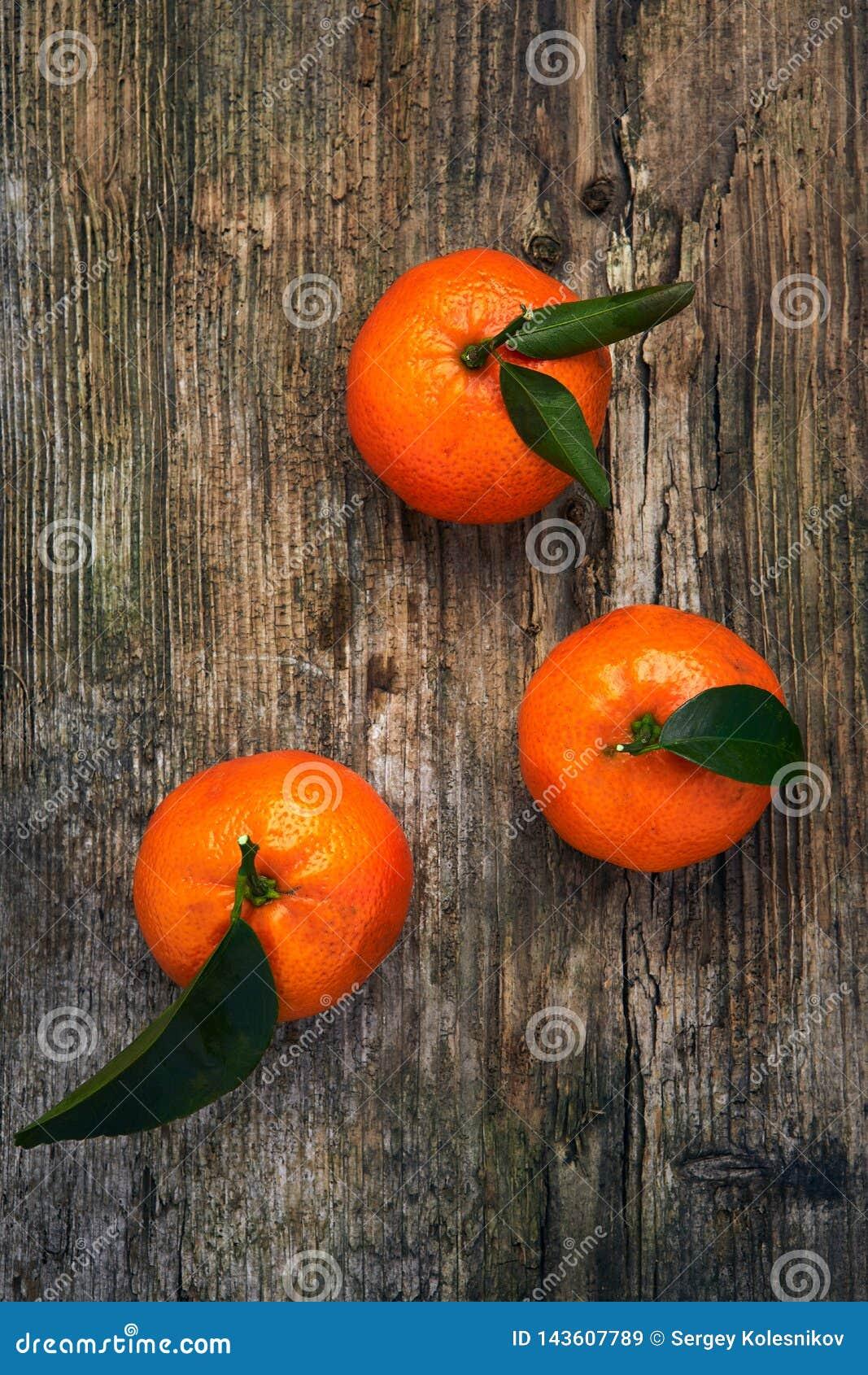 Laranjas, os mandarino, clementina, citrinas com as folhas no fundo de madeira