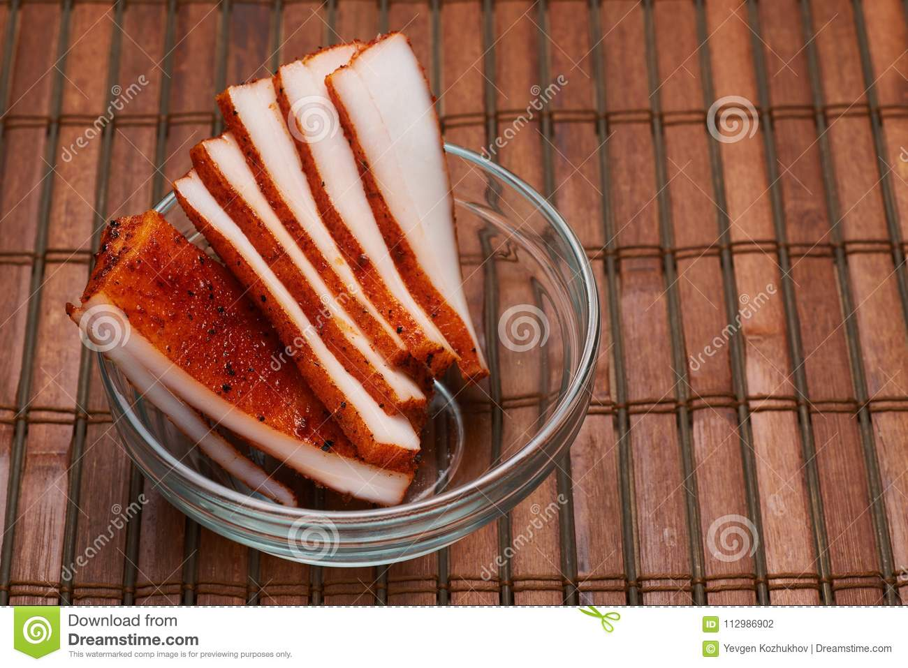 Lard with spices in a plate on a brown background