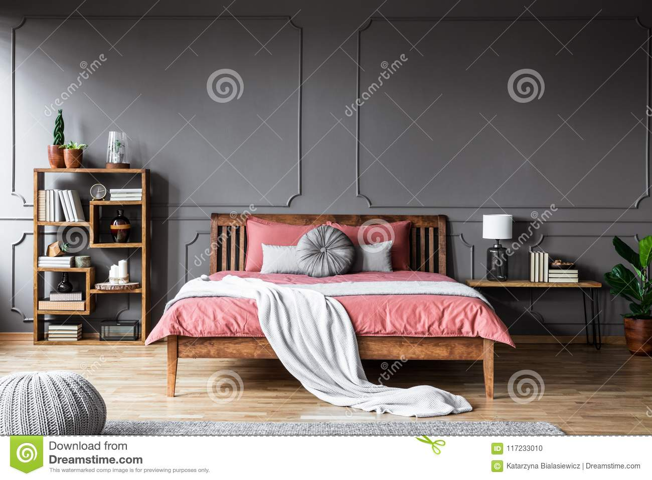 A large bed in a spacious, dark bedroom standing between a shelf