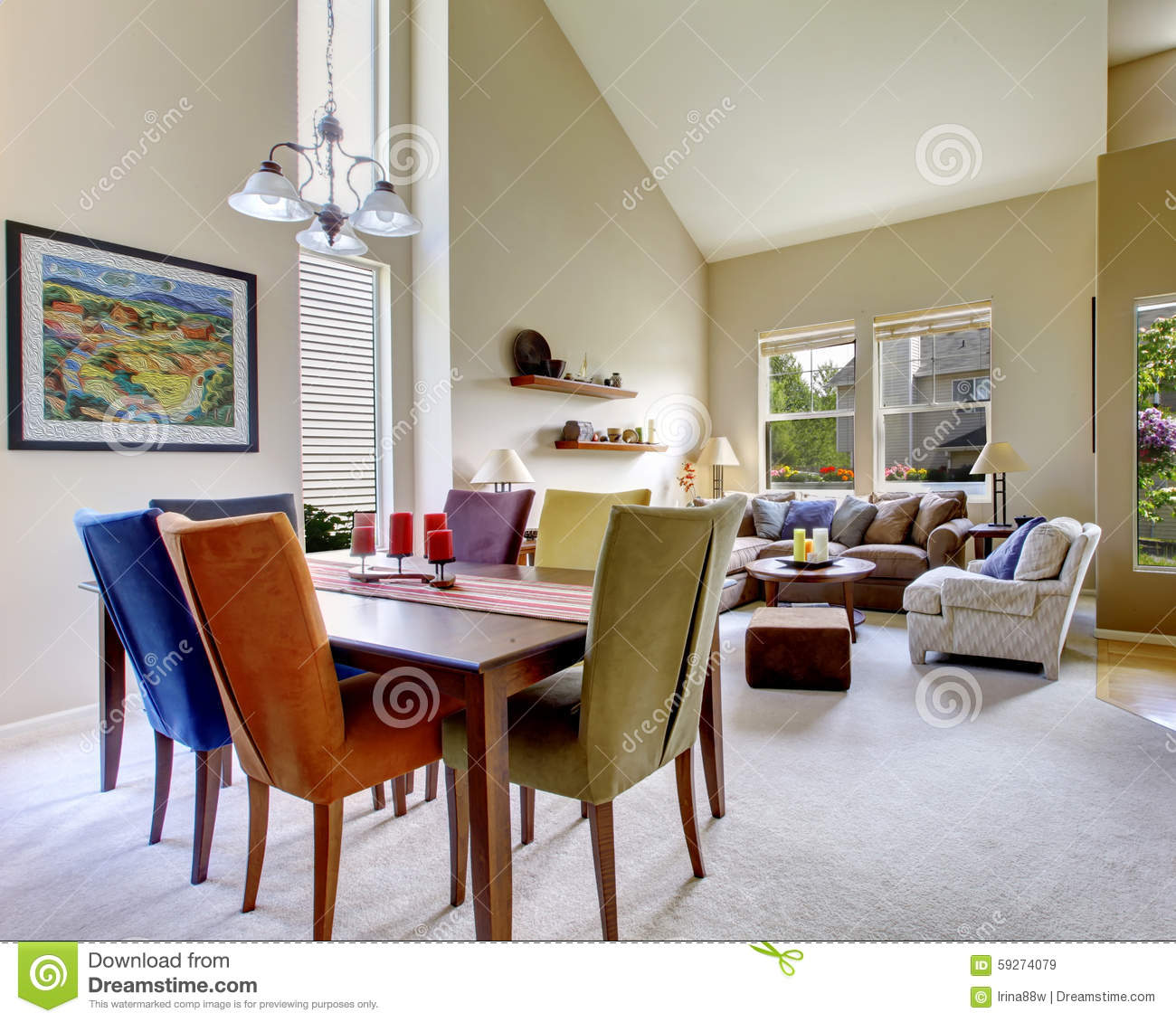 Large Beige Bright Living Room With Dining Room Table With Different Color  Chairs.