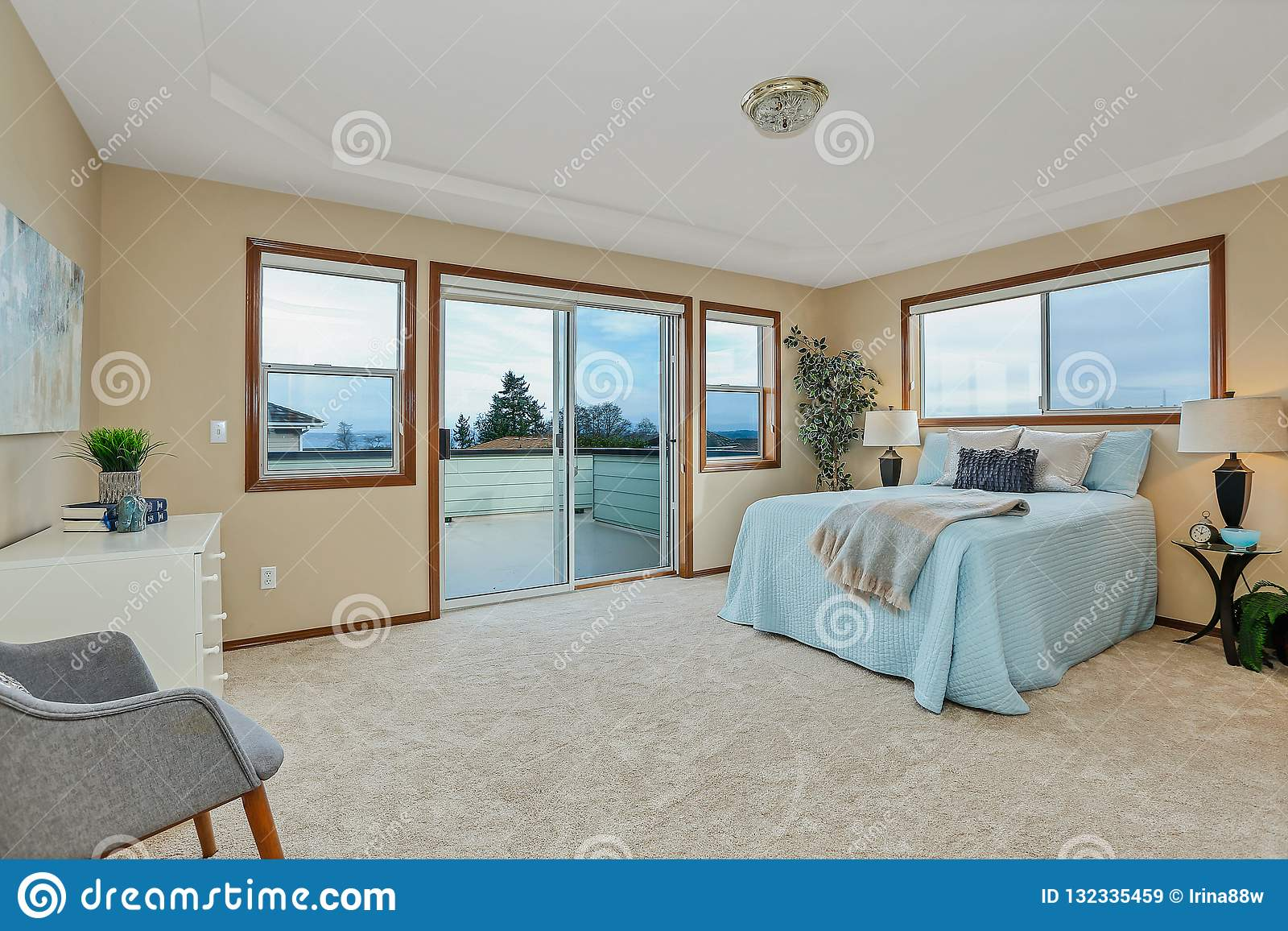 Large Beige Master Bedroom With Blue Bedding Stock Image Image Of Furnished Architecture 132335459