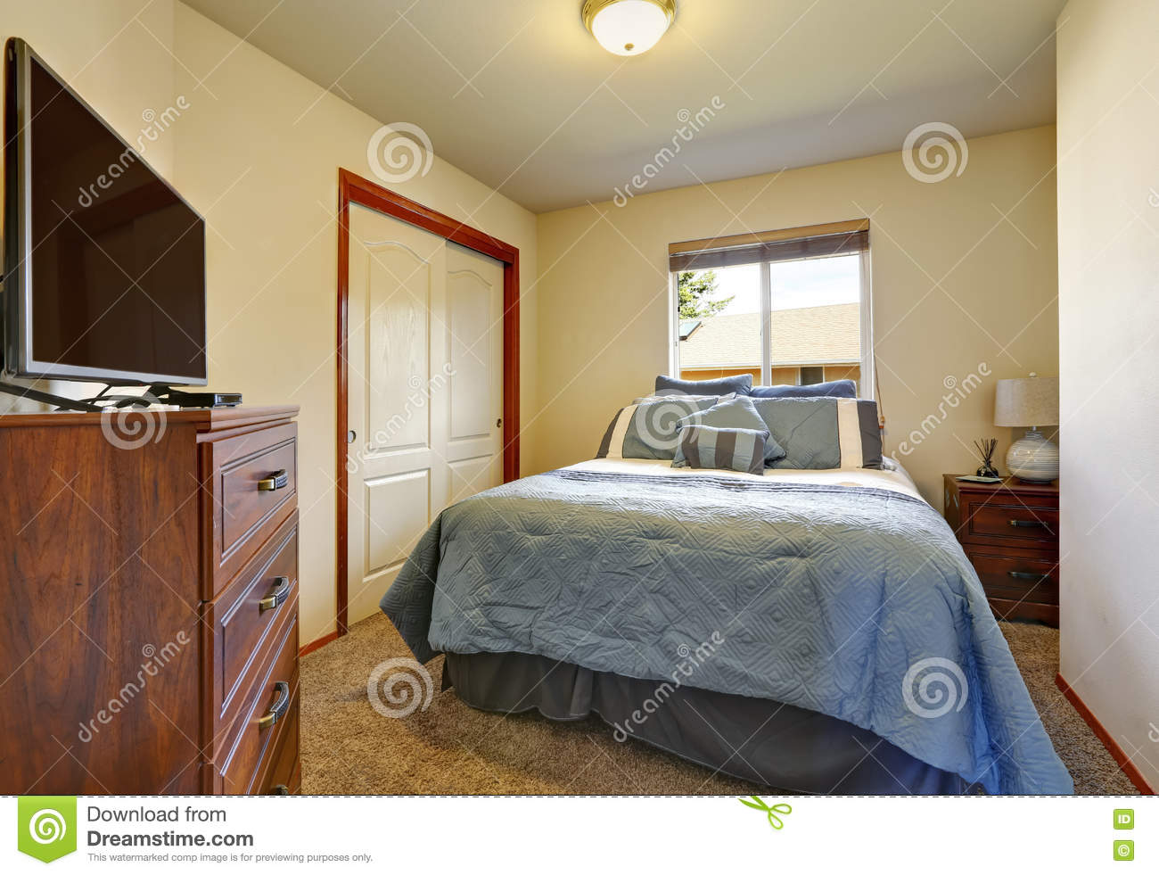 Large Blue Bed, Cabinet With TV, Closet In Small Bedroom Stock Photo ...