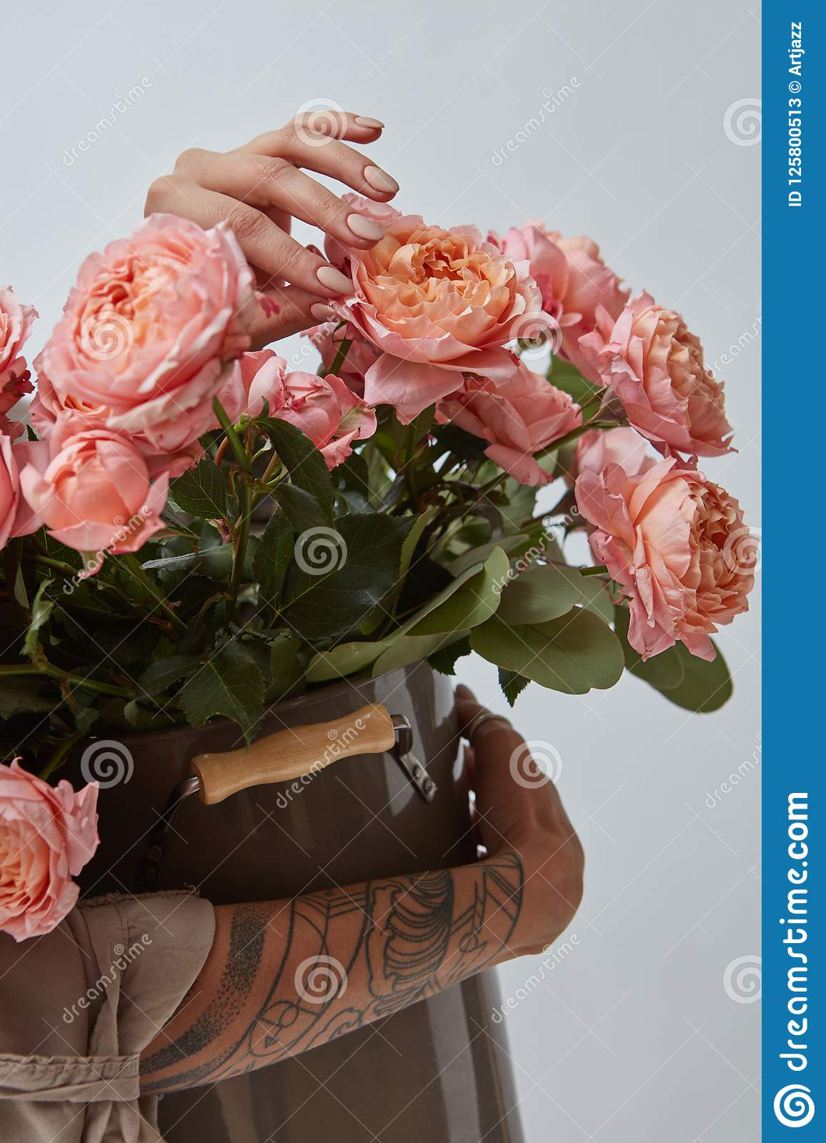 Female hands with tattoos holding a large brown vase with pink roses on a gray background. Flower shop