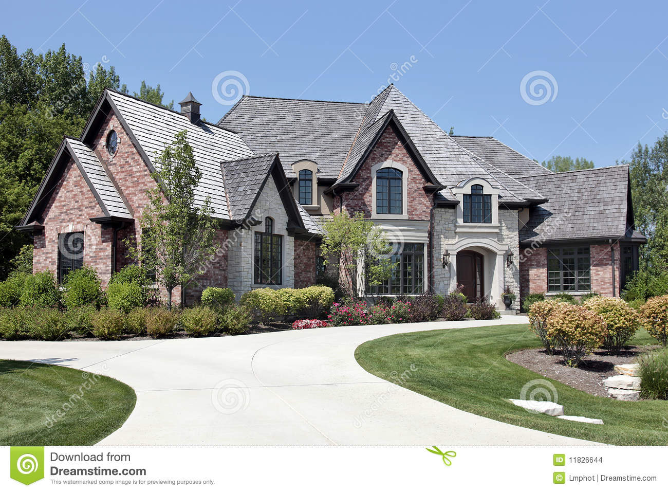 Large brick home with circular driveway stock photo for Brick home construction