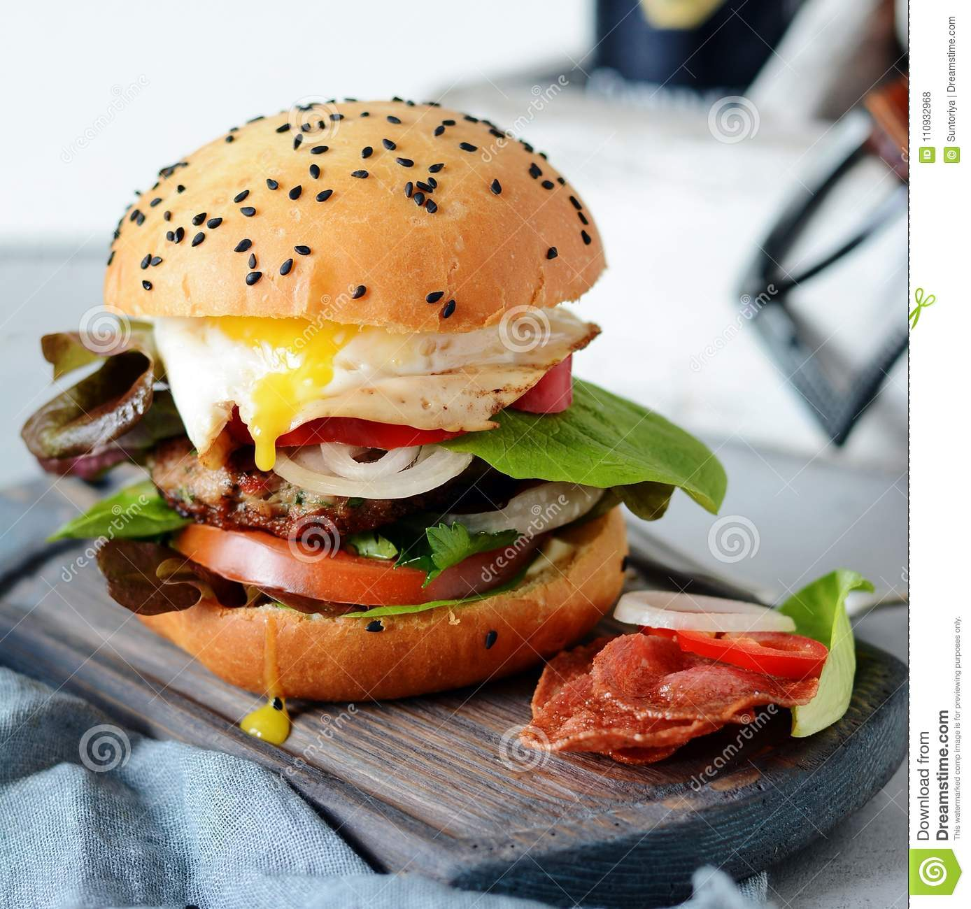 A large burger with a cutlet, vegetables, egg and a fresh roll. Sandwich for breakfast. Fast food. Men`s Food.