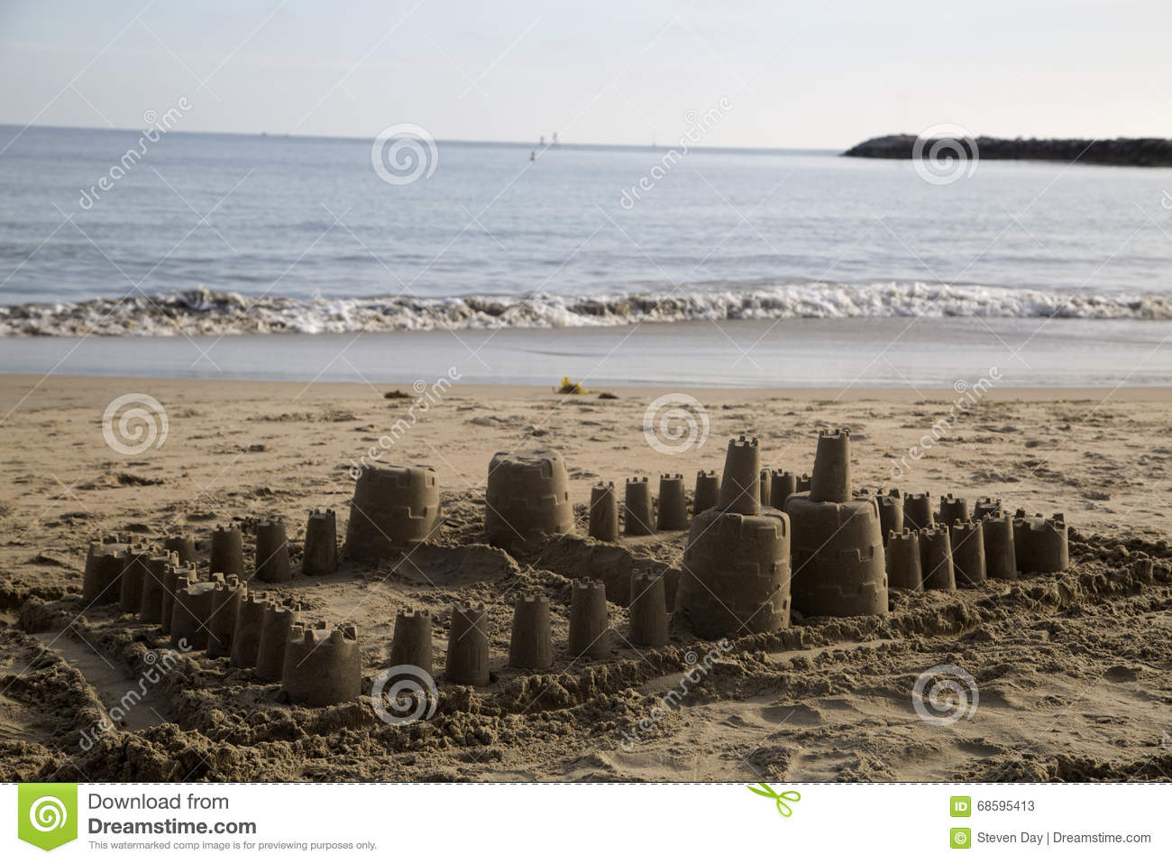 Large children s sand castle on the beach small ocean waves