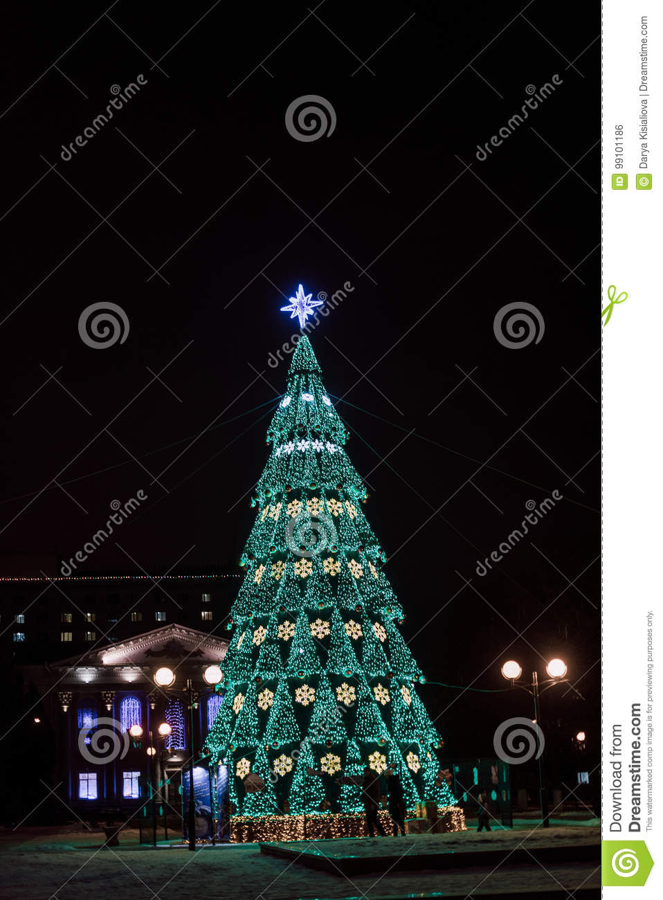 download a large christmas tree with bright garlands and star shine lights down on the street