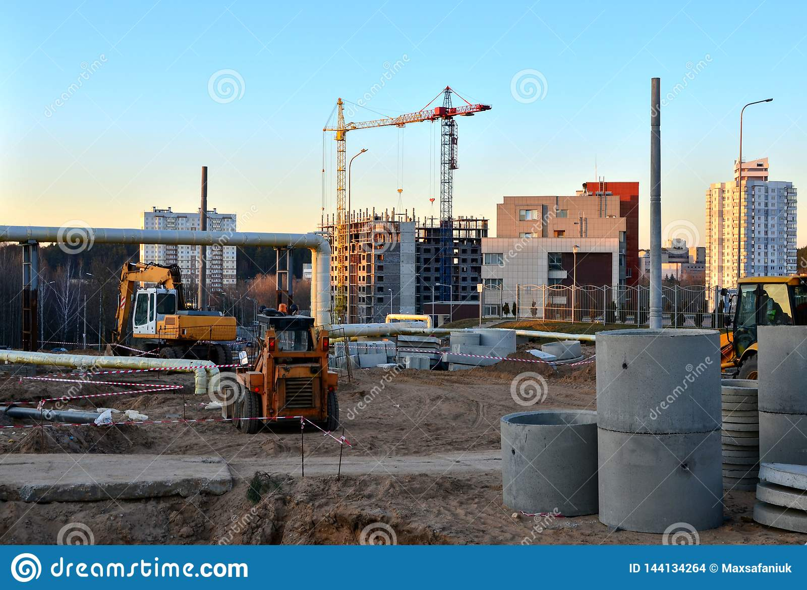Large construction site with working cranes and heavy machinery for road works, wheel loader, bulldozer, excavator.