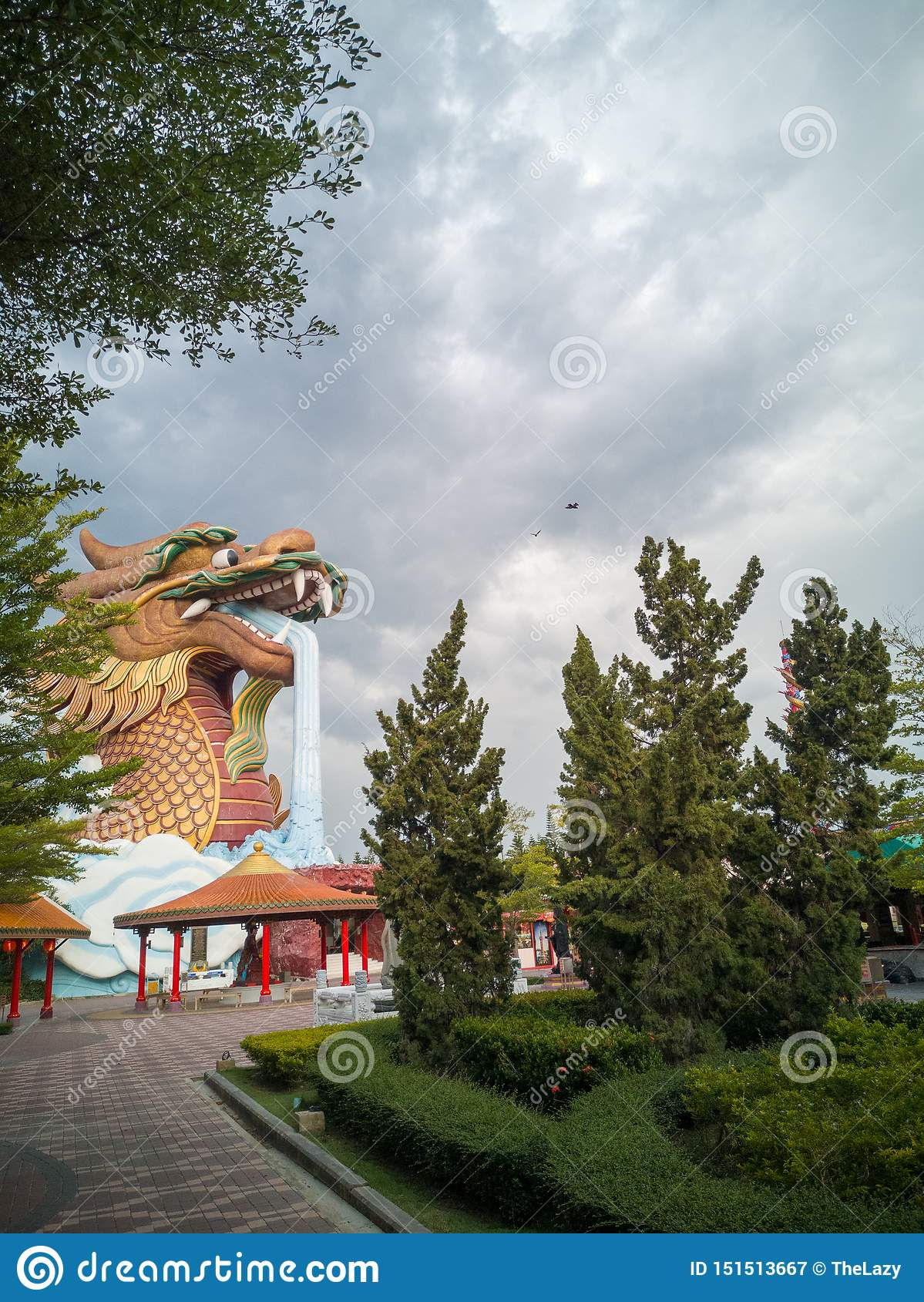 A large dragon building in the garden while the sky is near to rain