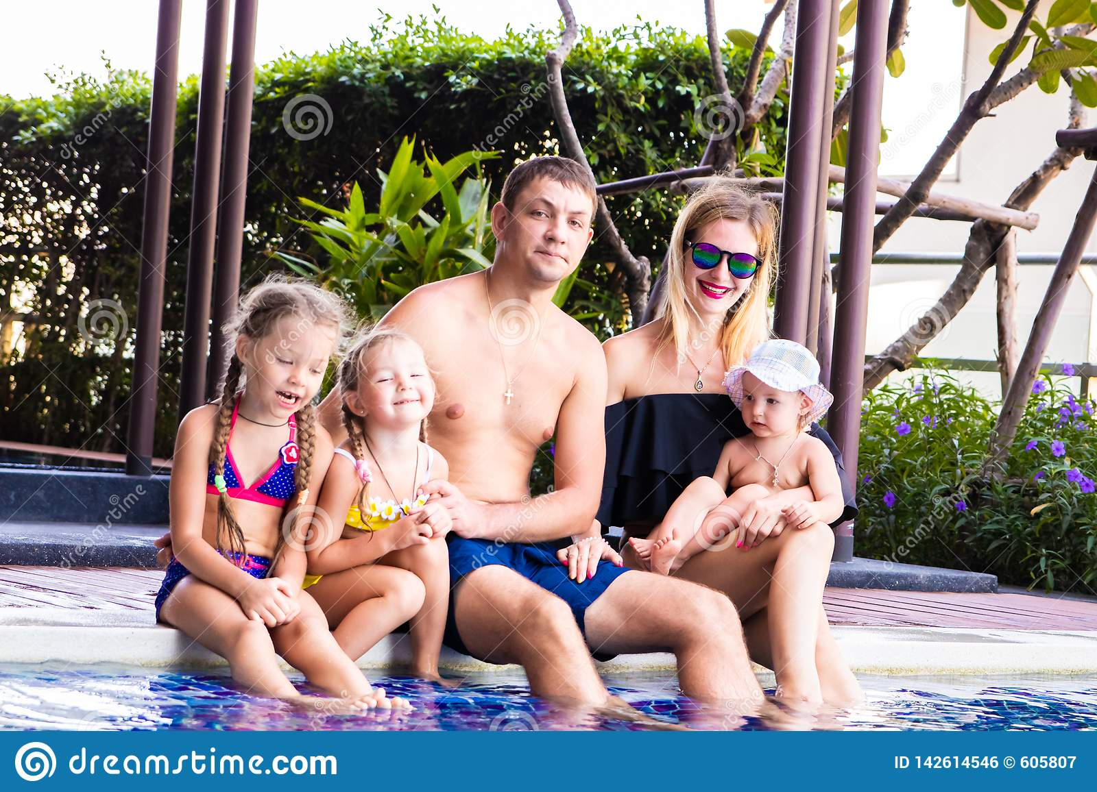 A large family sits by the pool in the villa. Mom, Dad and three daughters. The concept of a happy family, a large