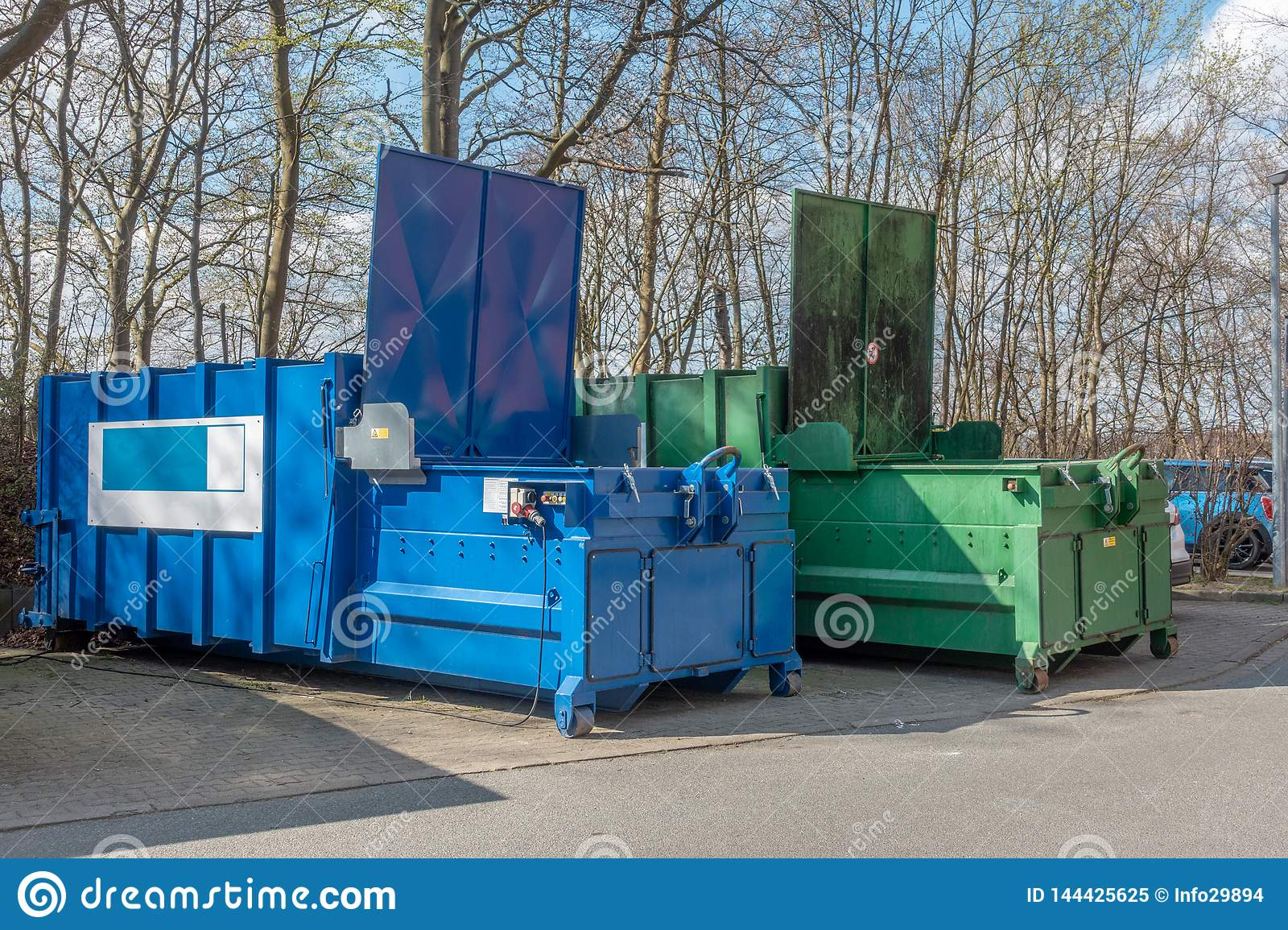 2 large garbage compactors standing on a hospital site