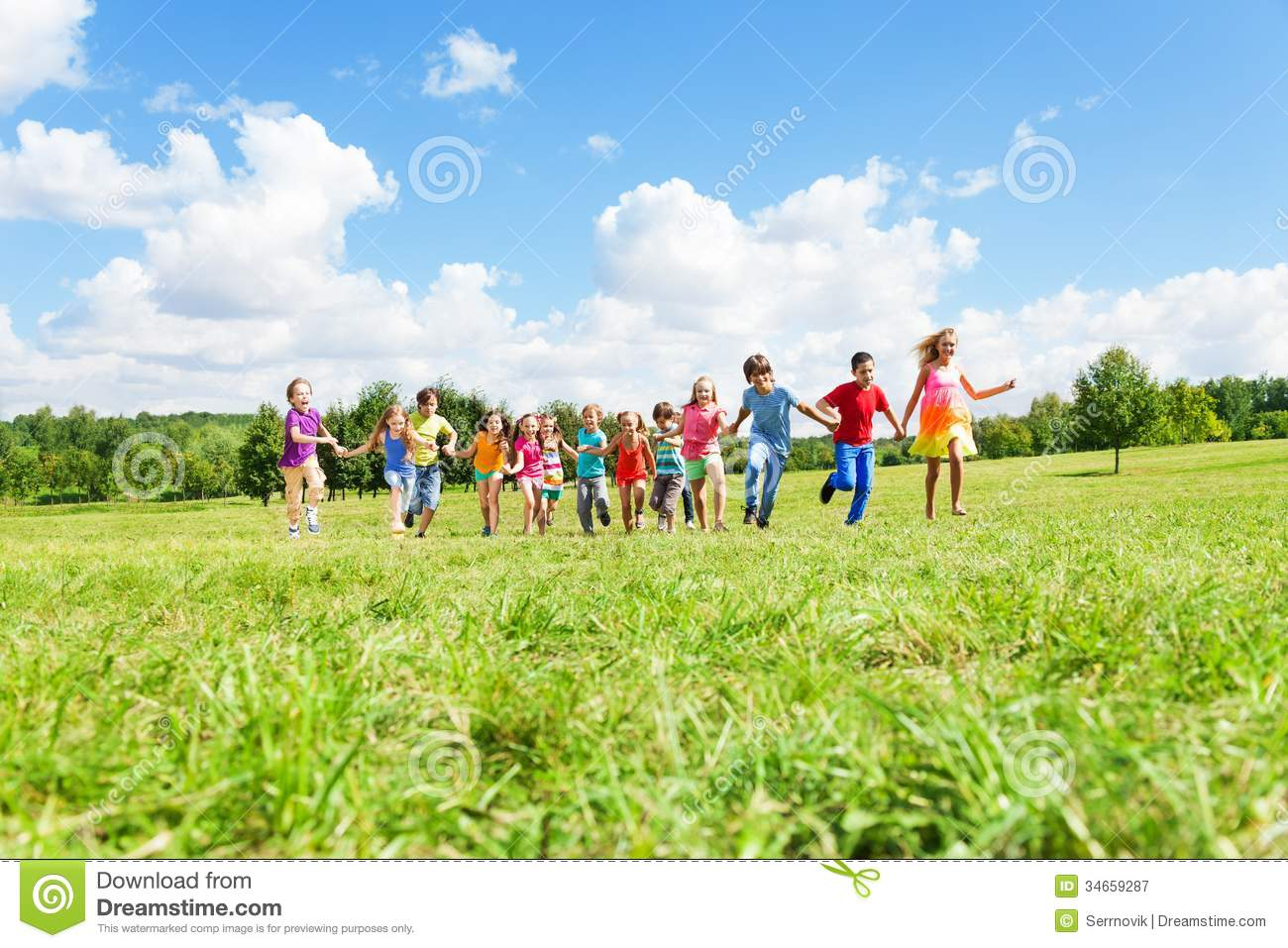 large group of kids running in the park royalty free stock