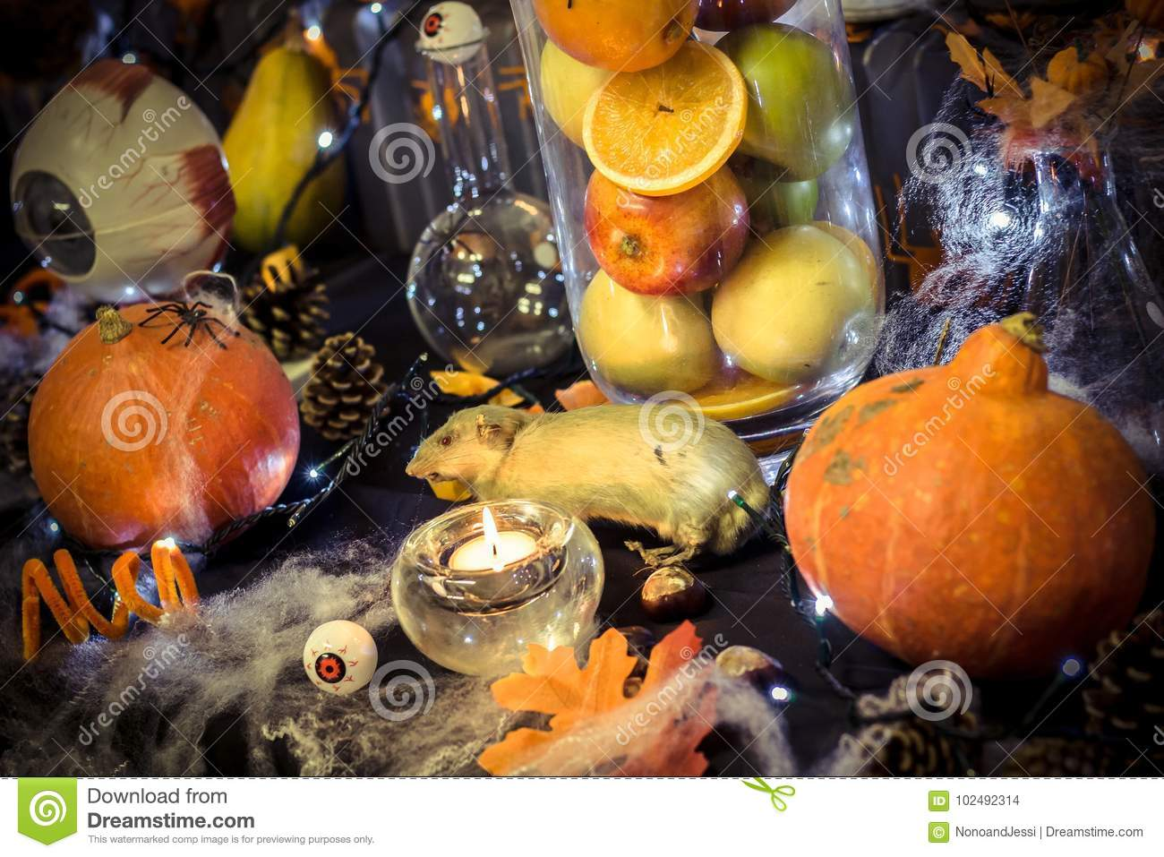 Large halloween decoration table with pumpkins, pine cone, a rat, candles, eyes, a light garland, a vase with fruits and cobwebs