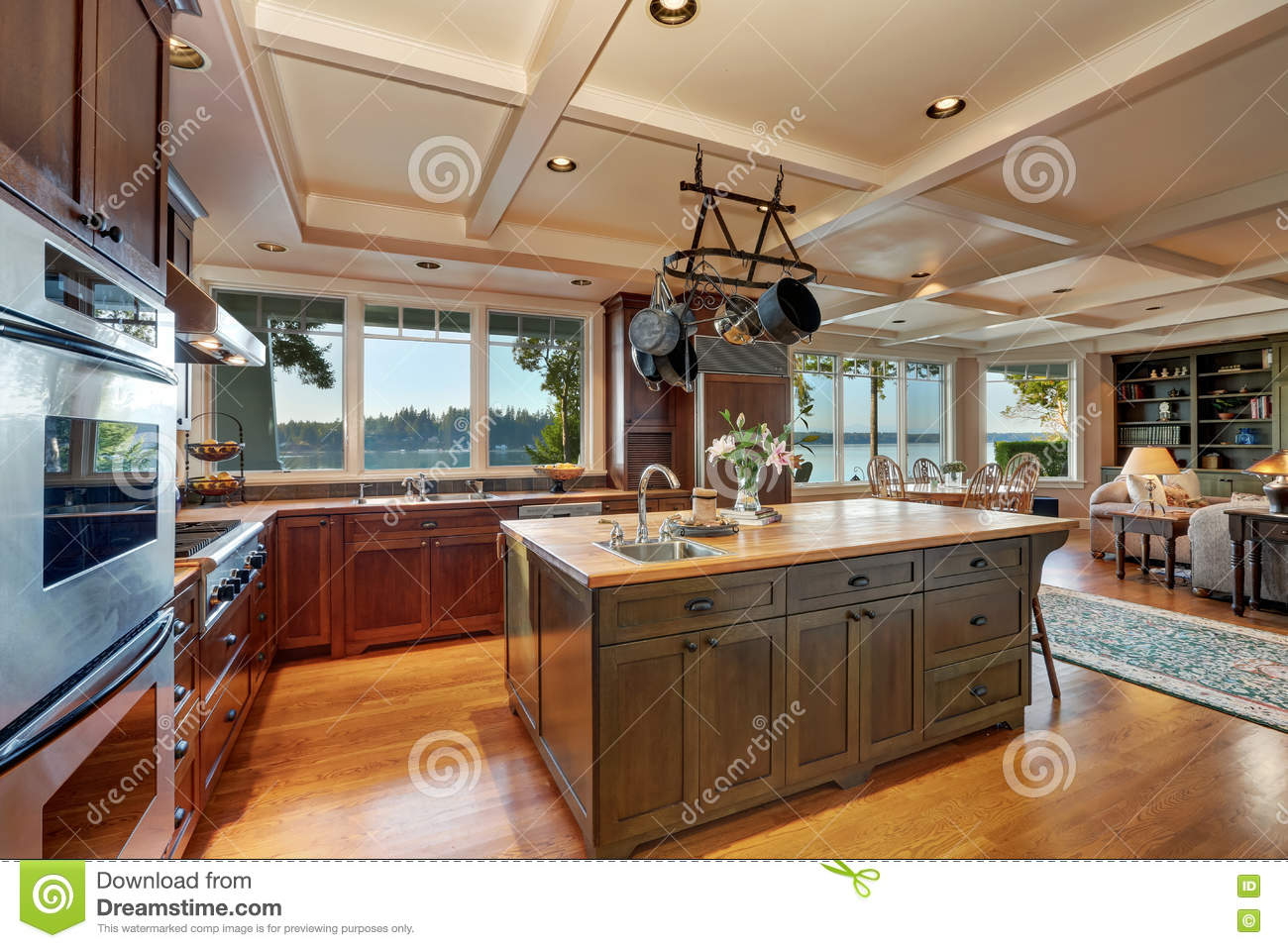 large kitchen island with hanging pot rack above stock photo