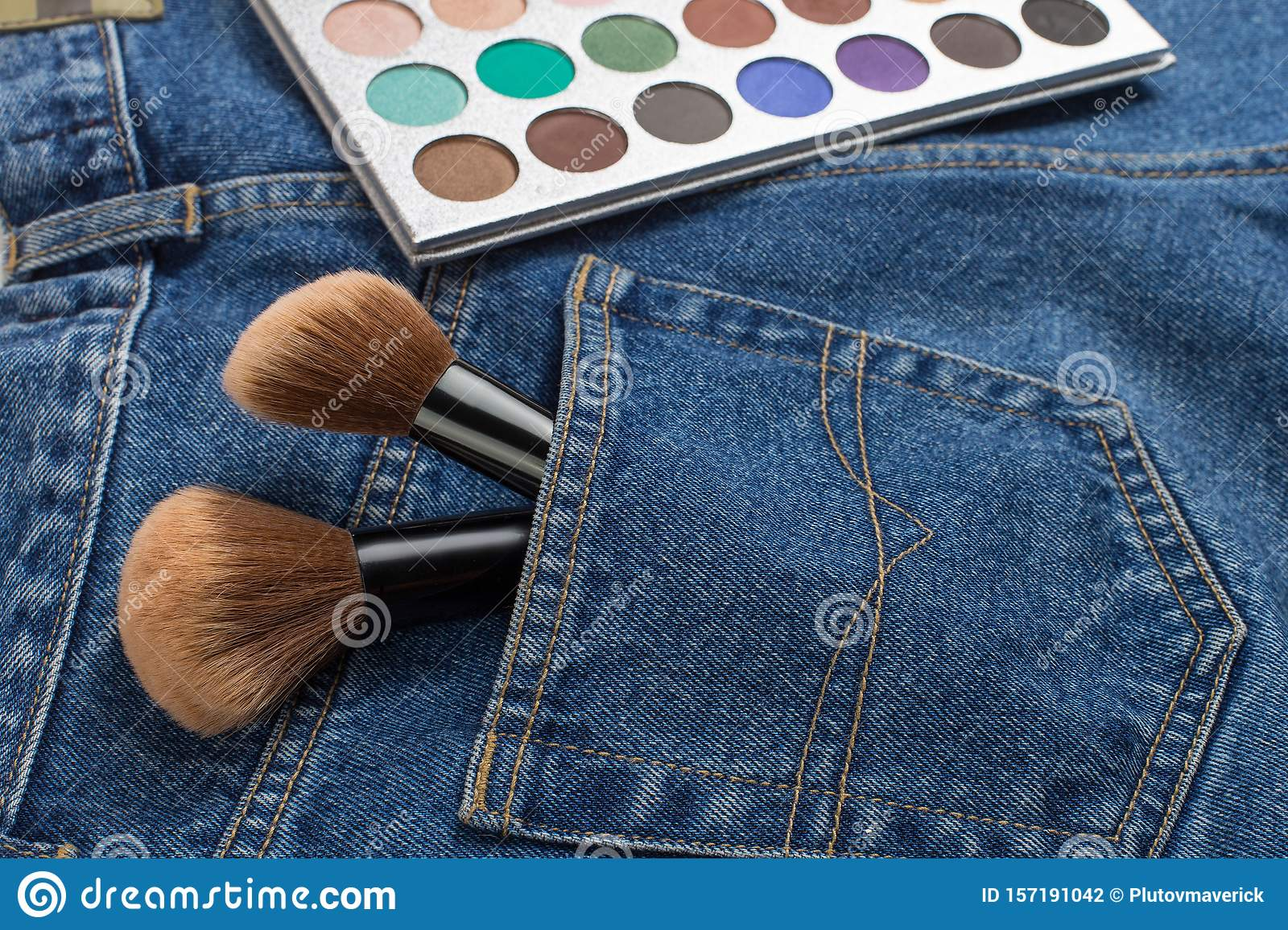 Large makeup brushes in a pocket of blue jeans. Concept, commercial work of a makeup artist, for printing business cards and