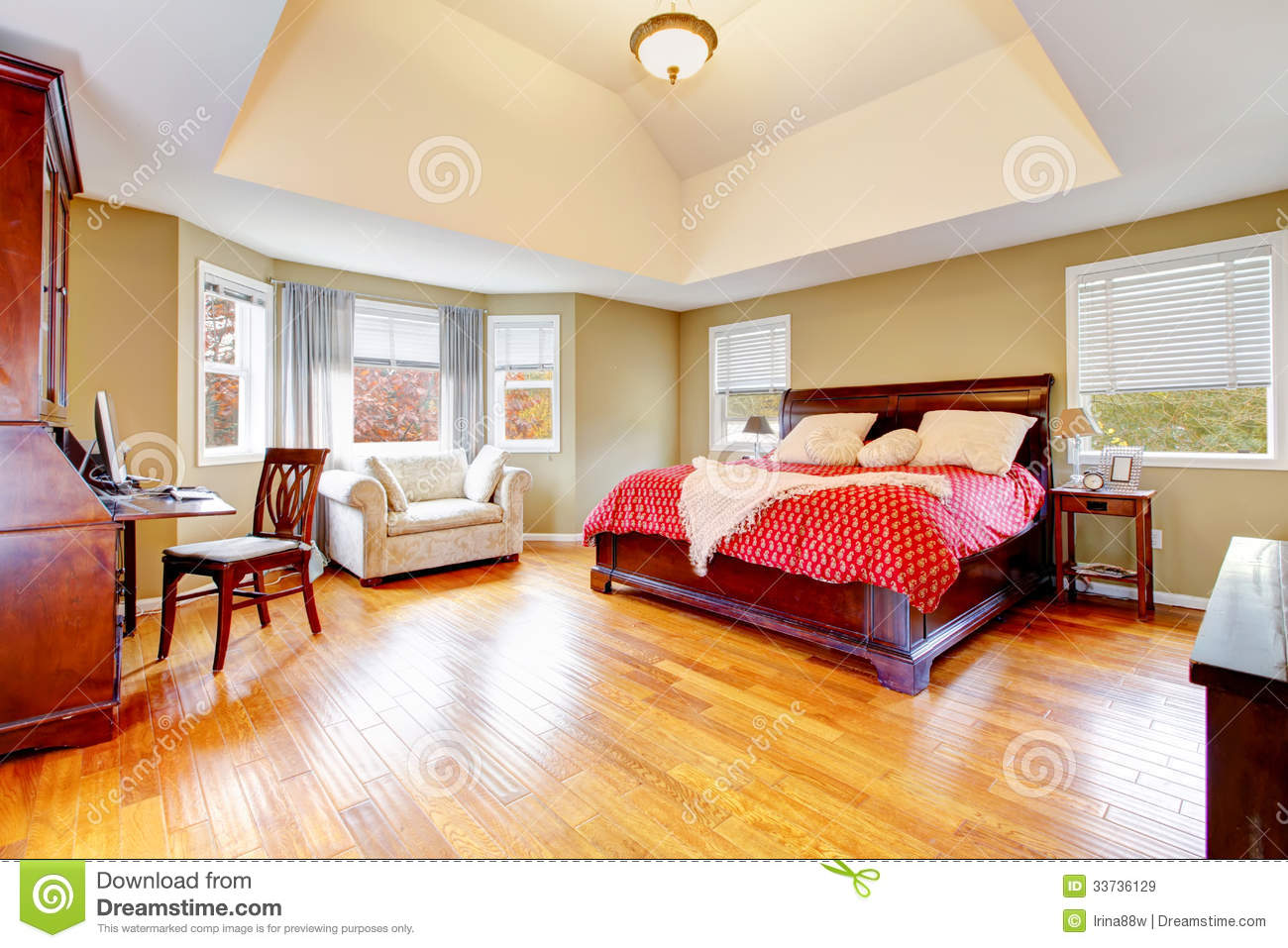 Large master bedroom interior with green alls and hardwood floor