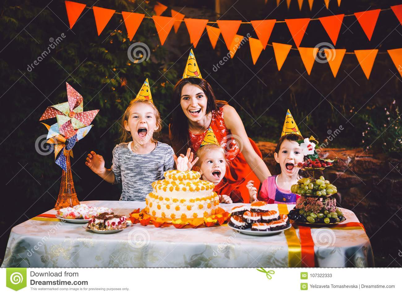 A large mother and three children at a festive table with sweets and a cake in the courtyard decorated with lights and a garland o