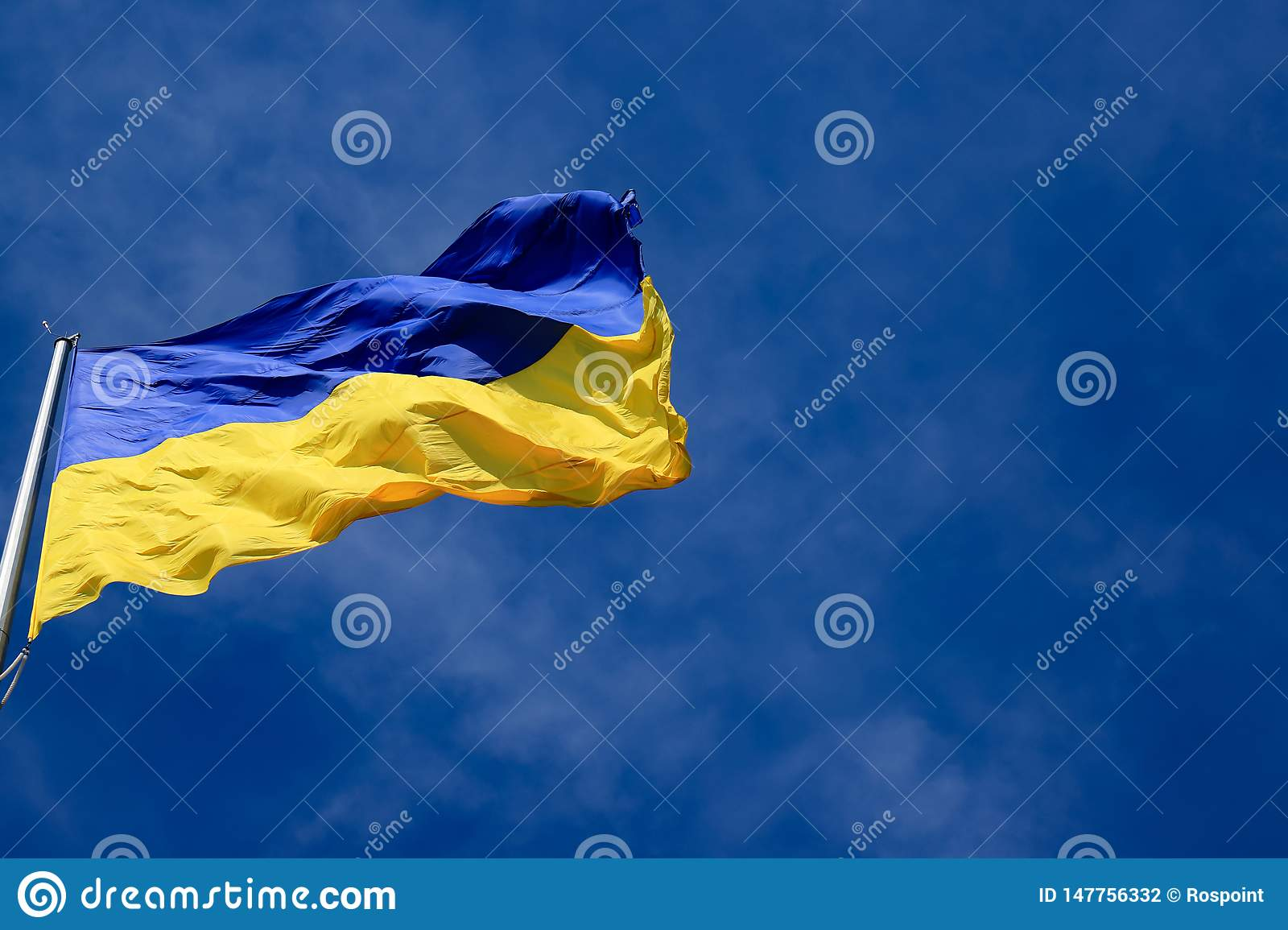 Large national flag of Ukraine in the blue sky. Big yellow blue Ukrainian state flag in the Dnepr city, Dnepropetrovsk