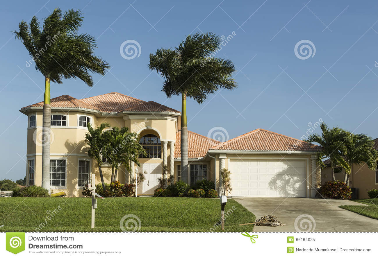 Large pink and yellow tropical house with circular driveway stock typical southwest florida concrete block and stucco home in the countryside with palm trees tropical plants and flowers grass lawn and pine trees florida mightylinksfo