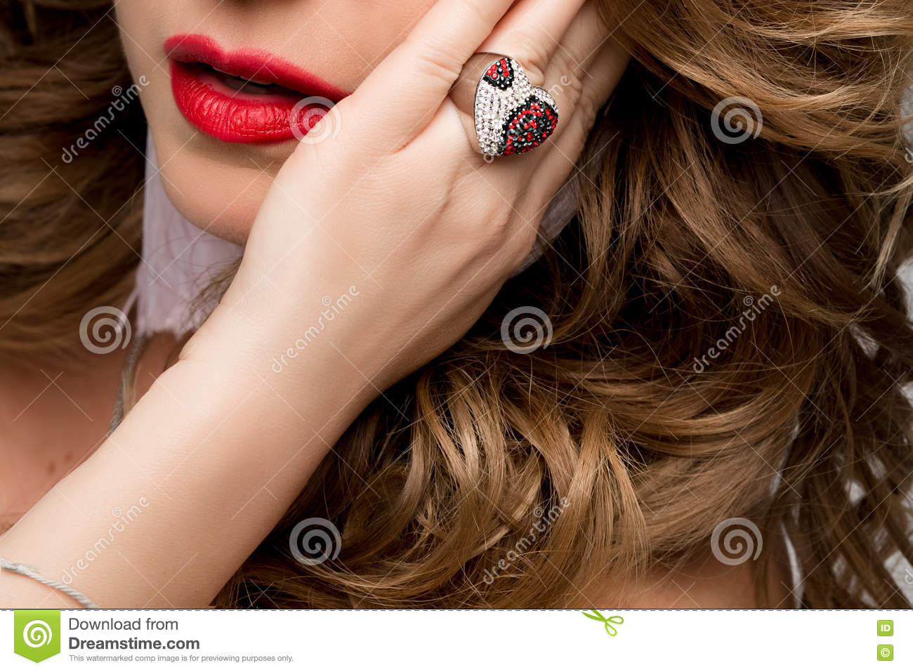 A large portrait of a woman s lips and the hand with the ring. Ring with precious stones, silver and red. Face, red lips