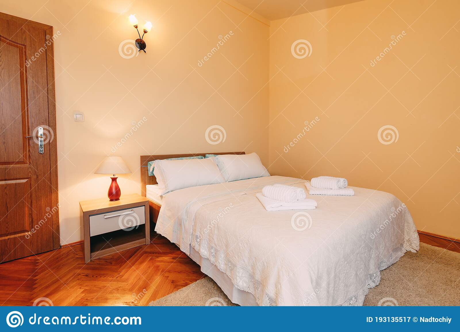 Picture of: Large Queen Size Bed With Pillows And Fluffy Towels On The Bedspread In A Spacious Room With Reading And Wall Lamps And Stock Image Image Of Curbstone House 193135517
