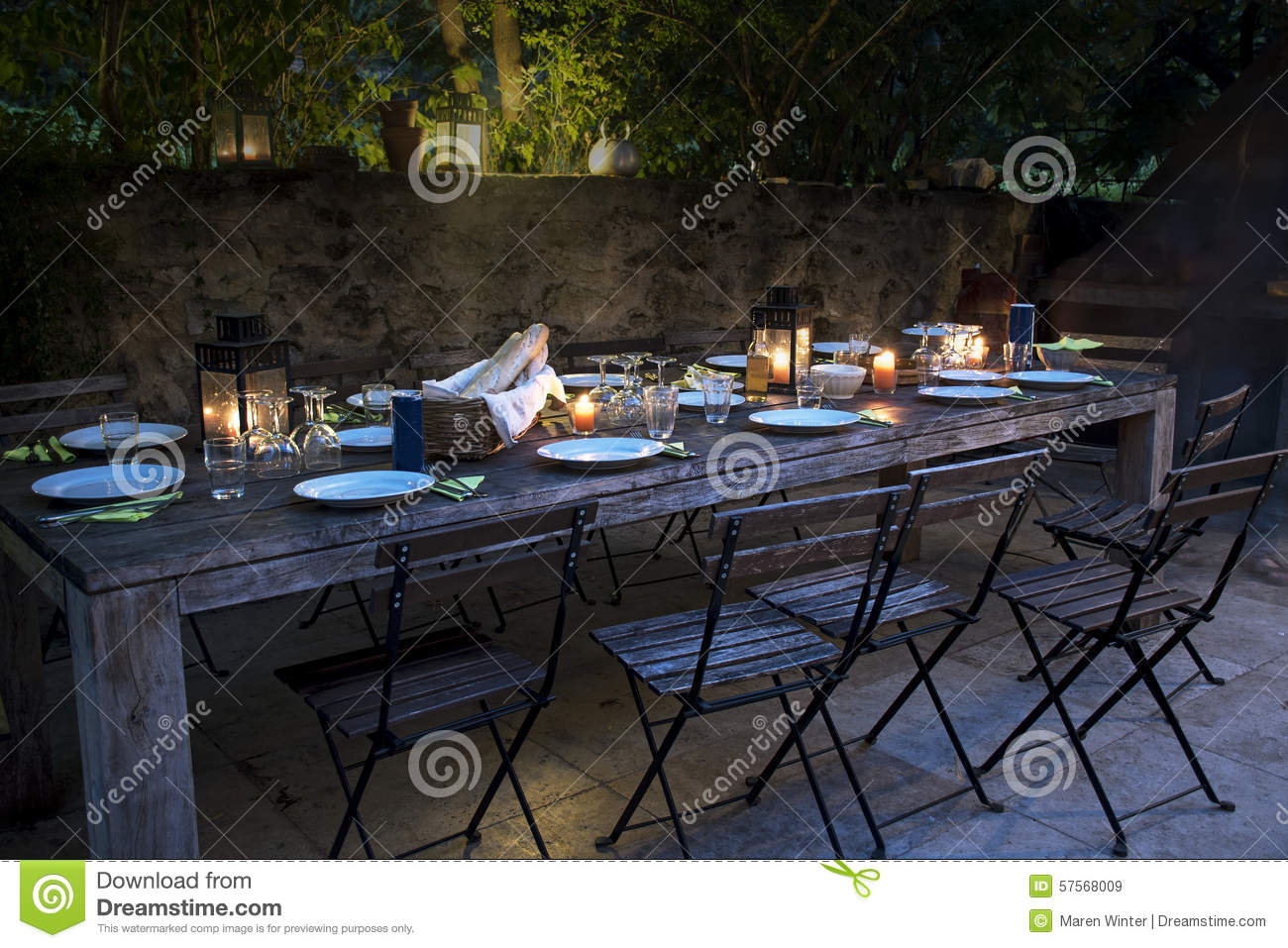 Large rustic table prepared for a outside dinner at night for Dinner on the terrace