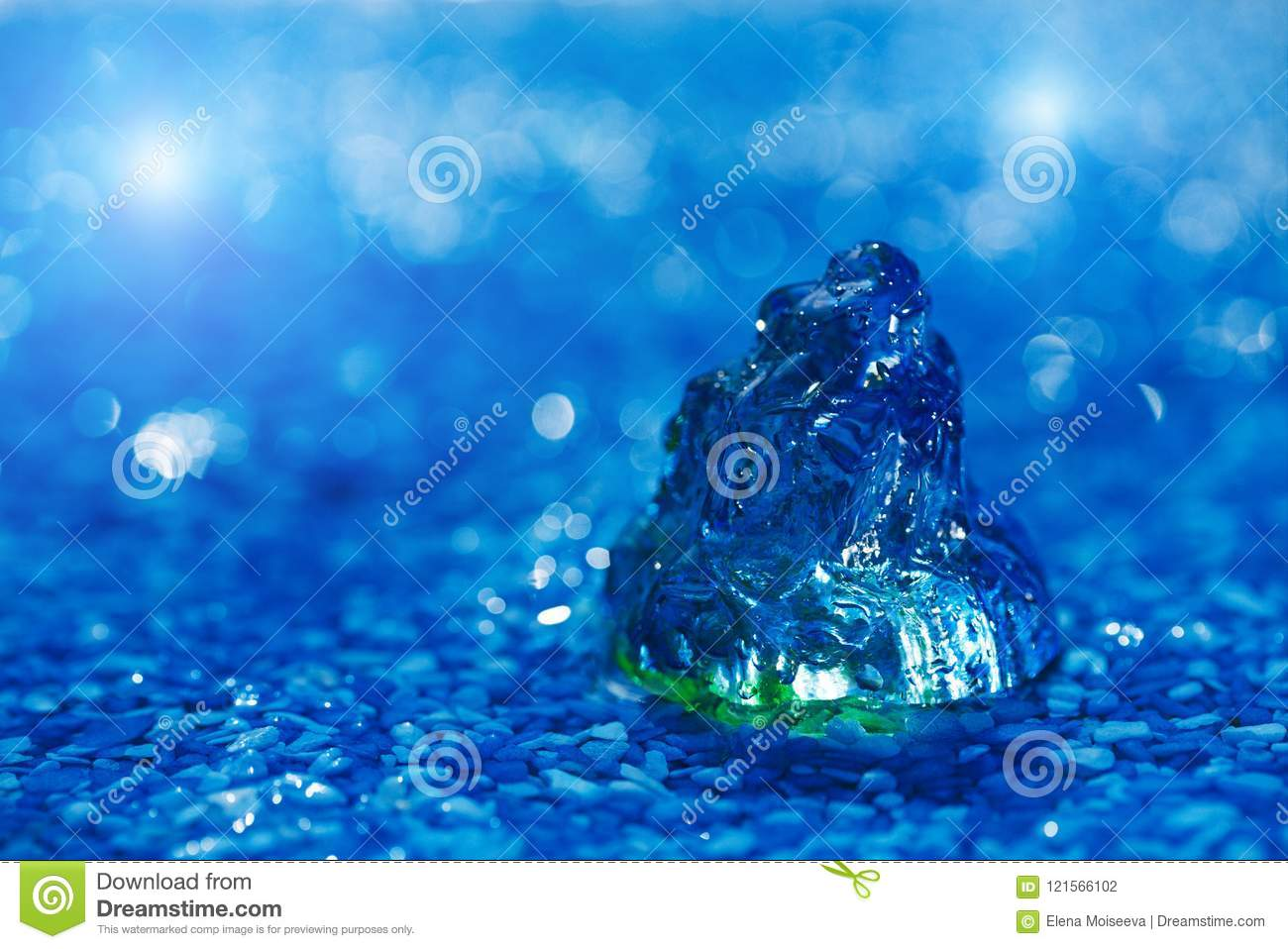 Large scallop glass sea shell on blue pebble under water droplet