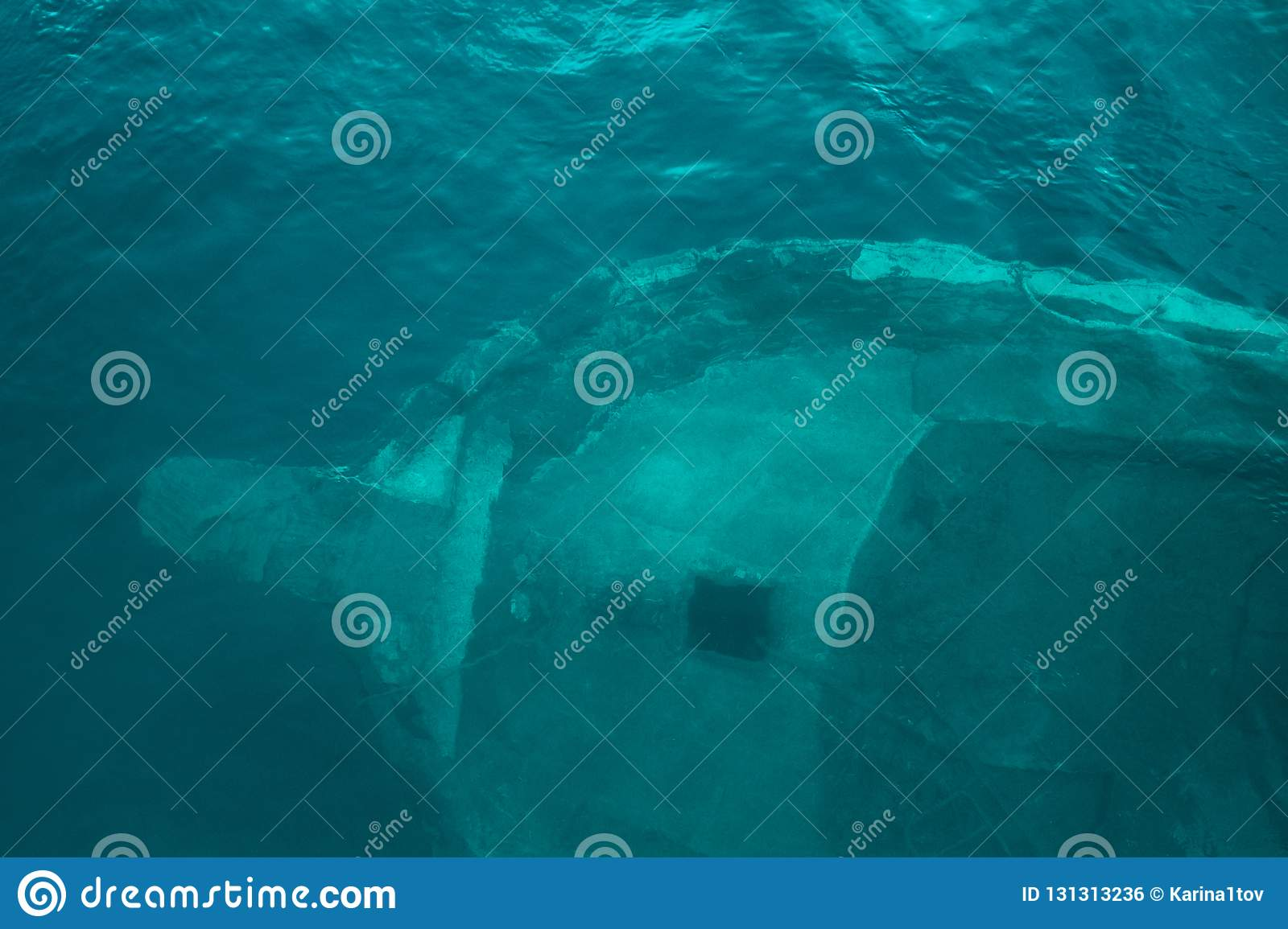 Large sunken ship, which is visible through the clear, blue water, view from the top.