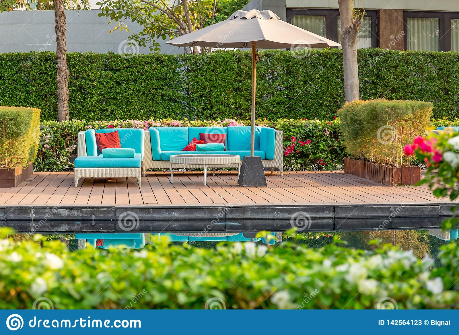 Large terrace patio with rattan furniture in the garden with umbrella.