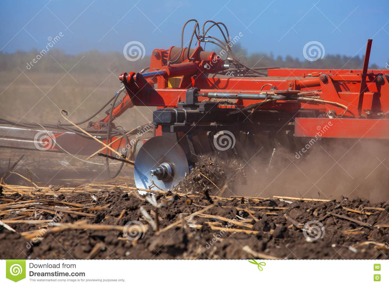 Large tractor pulling a plow and plow the field, remove the remnants of the previously beveled sunflower.