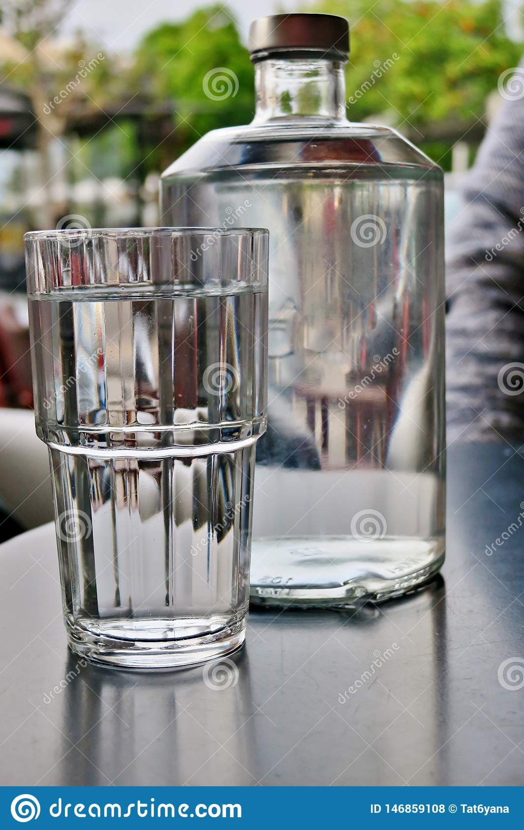 A large transparent bottle of water with a glass next, close-up