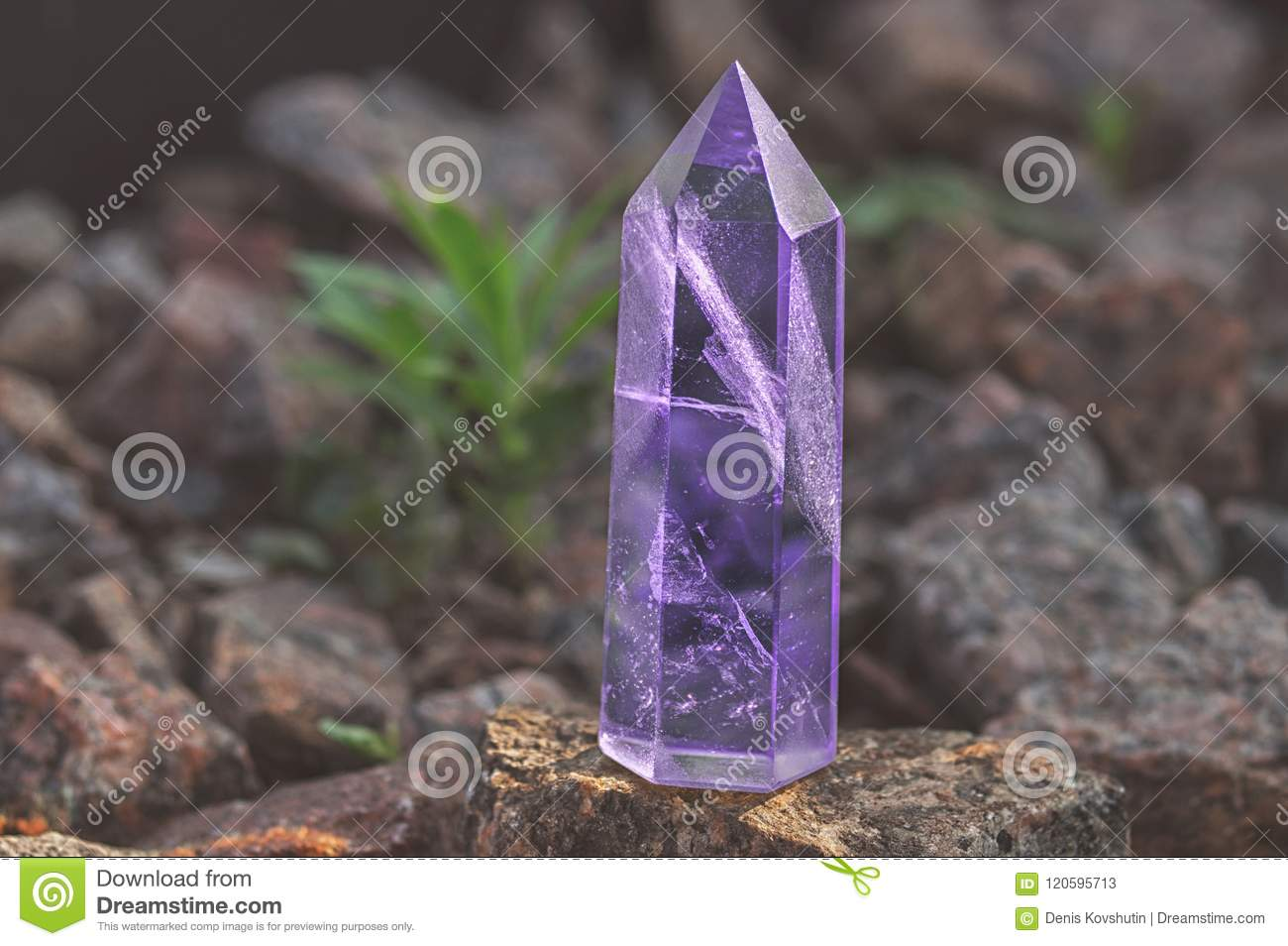 Large transparent mystical faceted crystal of colored lilac amethyst, chalcedony on a stone background close-up. Wonderful mineral