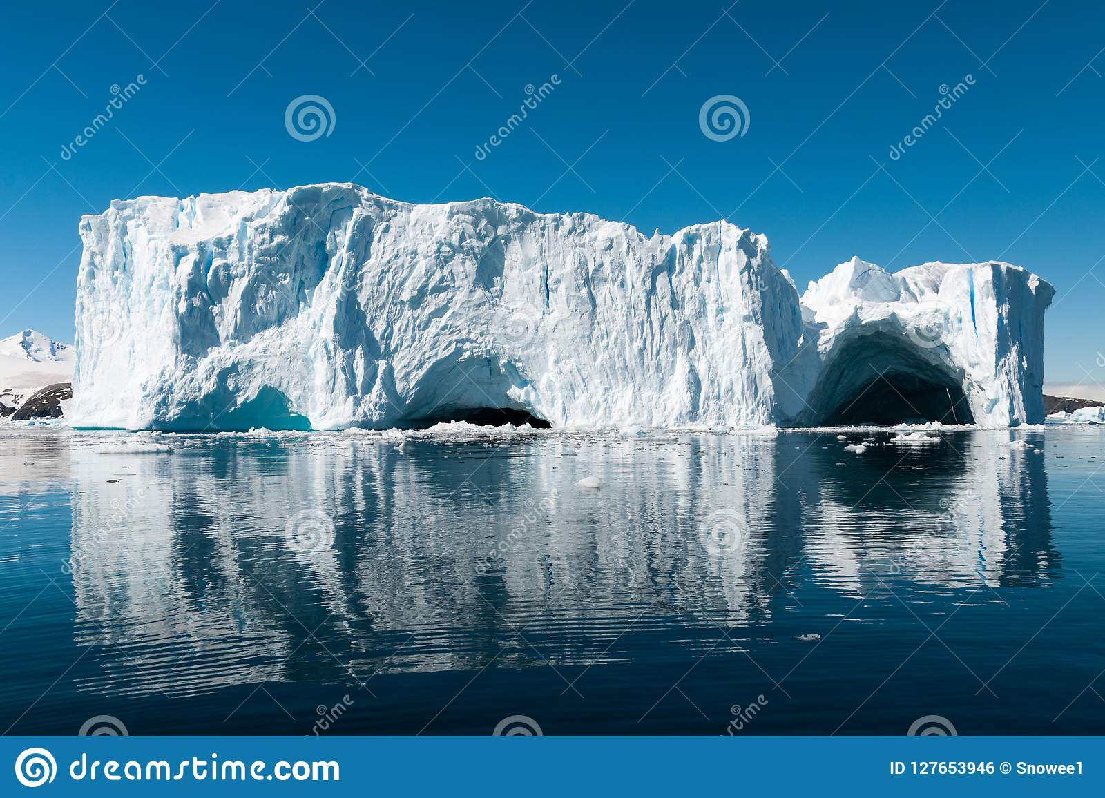 Large weathered iceberg with caves reflected in glassy water, Cierva Cove, Antarctic Peninsula