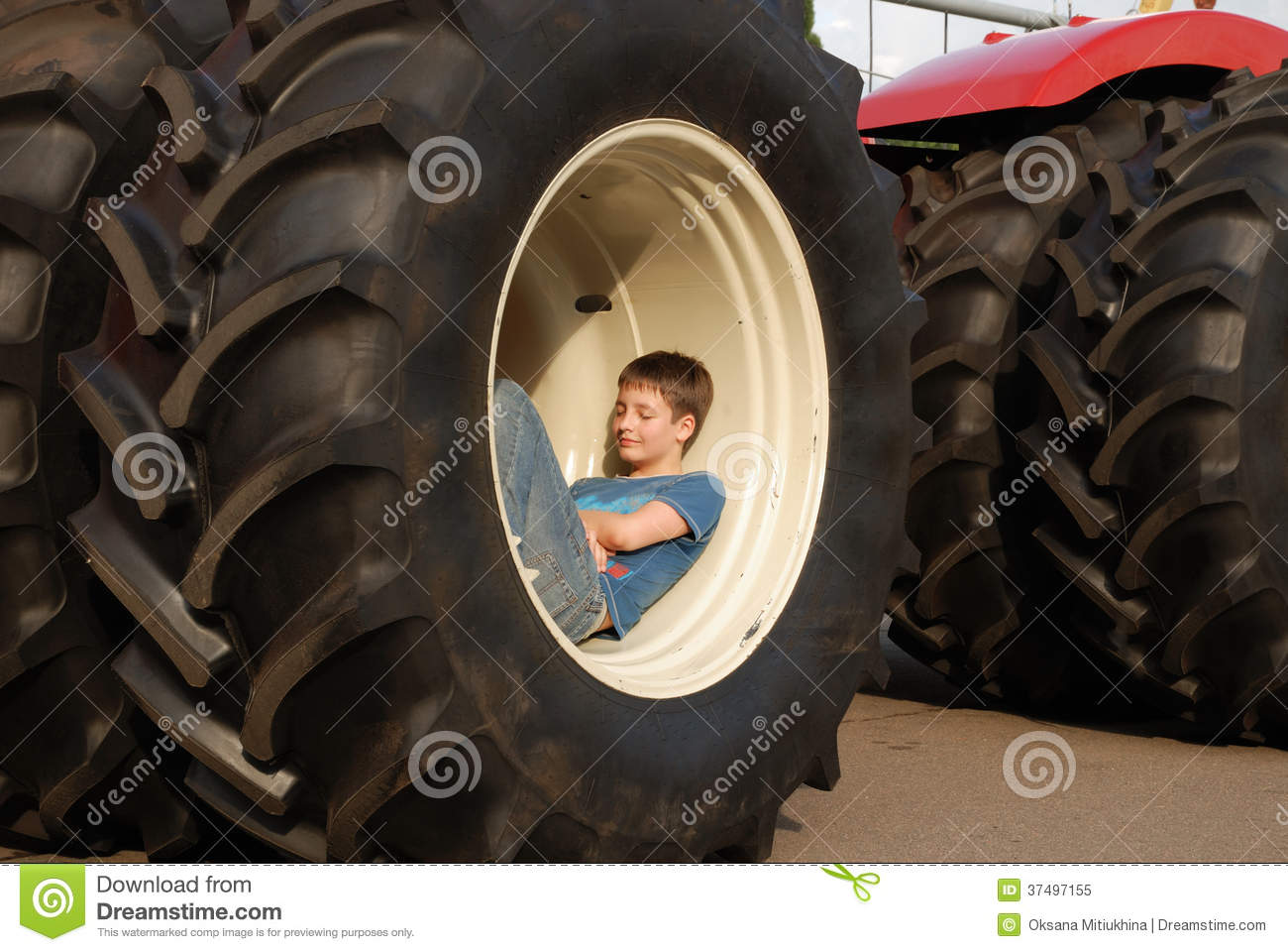 Large Tractor Wheels : Large wheels of tractor with a boy inside stock image