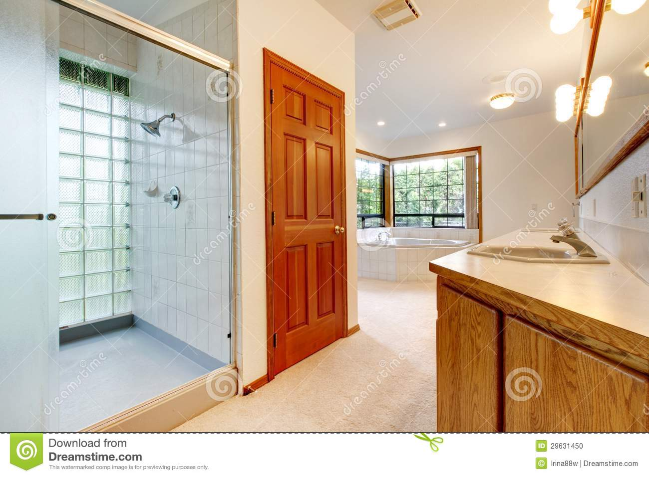 large white bathroom with tub shower and wood cabinet