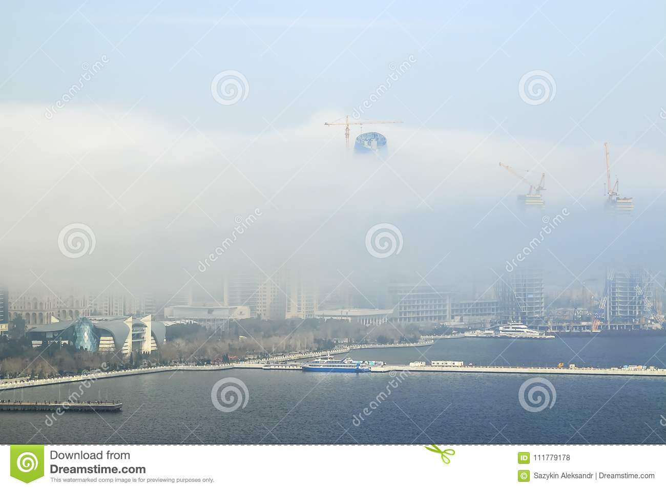 A large white cloud fell on the city and closed the view of the building. Foggy cloud moves from the sea to the city.