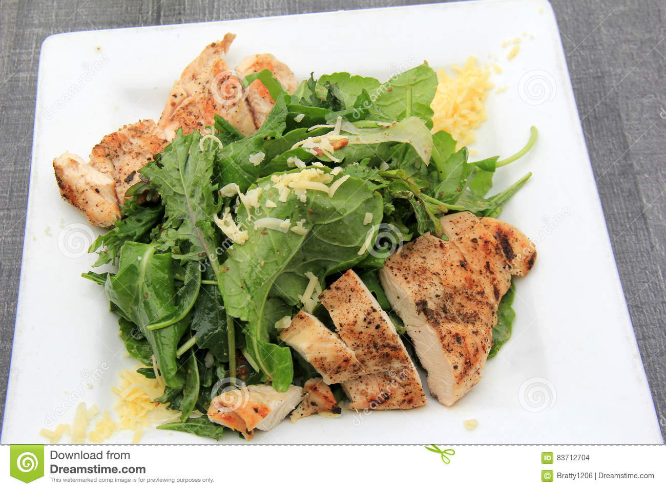 Large White Dish Covered With Grilled Chicken And Salad Greens Stock Photo