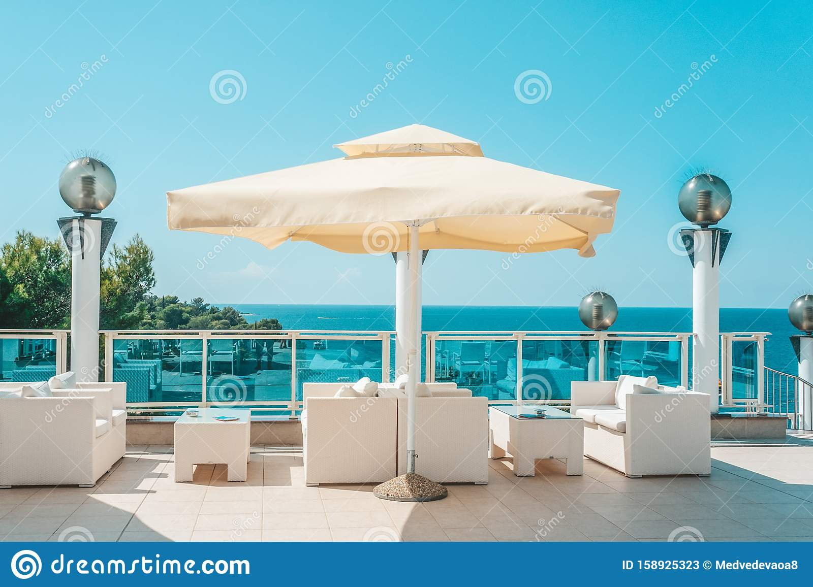 Large White Umbrella And Outdoor Furniture Sofas And Rattan Chairs With Cushions And A Glass Topped Table Place To Relax On The Stock Image Image Of Beach Glass 158925323